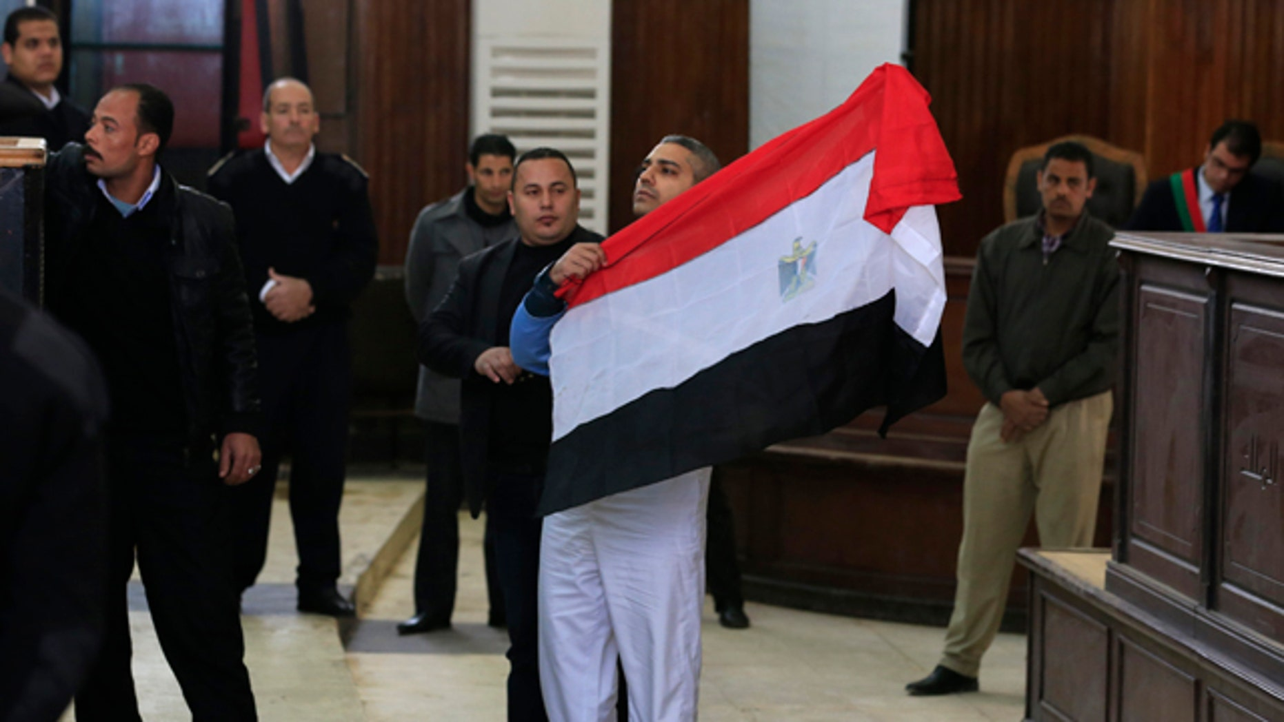 Feb. 12, 2015: Canadian Al-Jazeera English journalist Mohamed Fahmy holds up an Egyptian flag at a courthouse near Tora prison in Cairo. (AP Photo/Hassan Ammar)