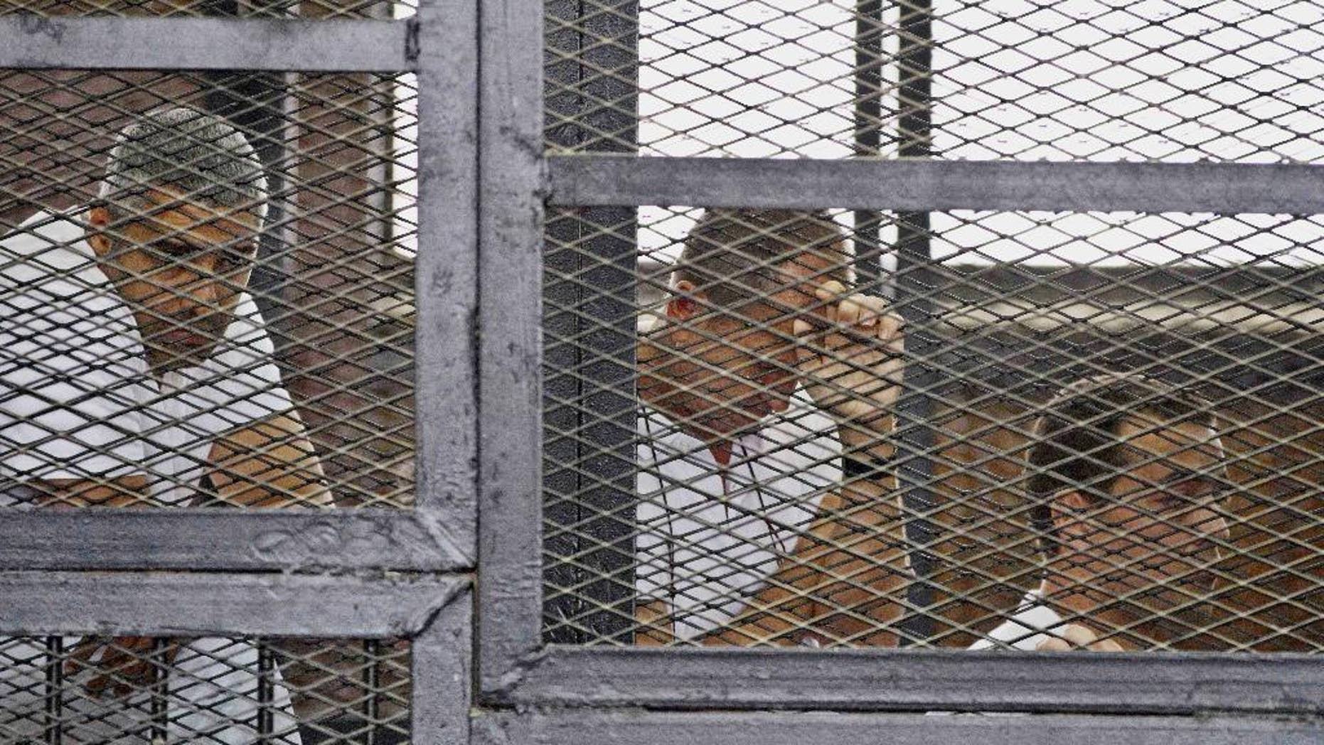 FILE - In this Thursday, May 15, 2014 file photo, from left, Mohammed Fahmy, Canadian-Egyptian acting bureau chief of Al-Jazeera, Australian correspondent Peter Greste, and Egyptian producer Baher Mohamed appear in a defendant's cage along with several other defendants during their trial on terror charges at a courtroom in Cairo. Egypt's state news agency says the trial of three Al-Jazeera English journalists and 17 others has adjourned until next week when the judge will deliver the verdict, five months after the trial opened. Fahmy, Greste and Baher have been in detention since December 29. (AP Photo/Hamada Elrasam, File)