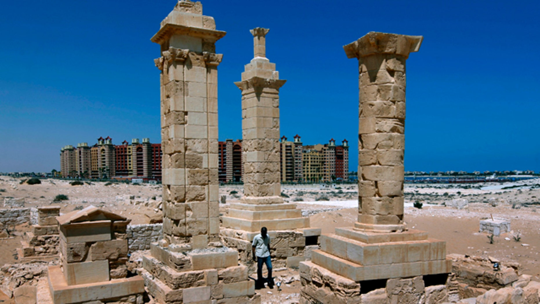 With a five star hotel in the background, a man walks by restored Roman pillar tombs of the ancient city of Leukaspis a well known Greco-Roman port overlooking the Mediterranean Sea at the costal resorts of Marina,  Egypt Sunday, Aug. 29, 2010. Today, it's a sprawl of luxury vacation homes where Egypt's wealthy play on the white beaches of the Mediterranean coast. But 2,000 years ago, this was a thriving Greco-Roman port city, boasting villas of merchants grown rich on the wheat and olive trade.