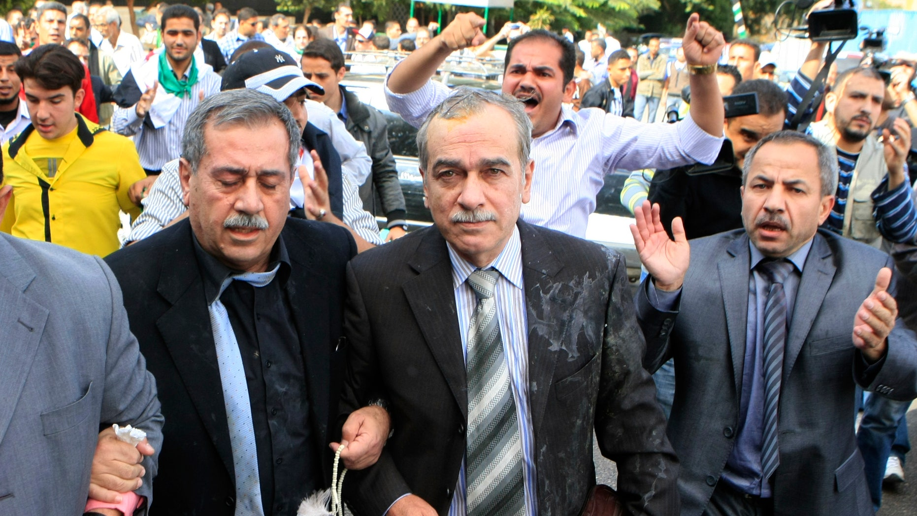 Nov. 9, 2011: Syrian protesters throw eggs toward Abdul-Aziz al-Khair, a member of the Syrian National Coordination Committee, center, and other opposition leaders as they try to enter the Arab League headquarters where they were to hold talks with the organization's chief on violence in Syria, in Cairo, Egypt.
