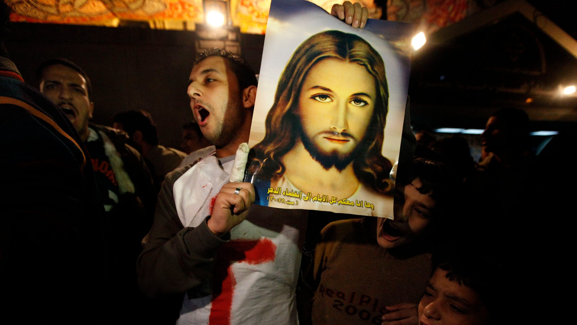 Jan. 3: Angry Copts carry a picture of Jesus Christ and chant anti government slogans during a protest before clashing with Egyptian riot police, unseen in Cairo, Egypt late Monday. The head of Egypt's Coptic Orthodox Church appealed to the government on Monday to address Christians complaints about discrimination to ease tensions as fierce riots broke out in the capital following a New Year's Day church bombing that killed 21 people.
