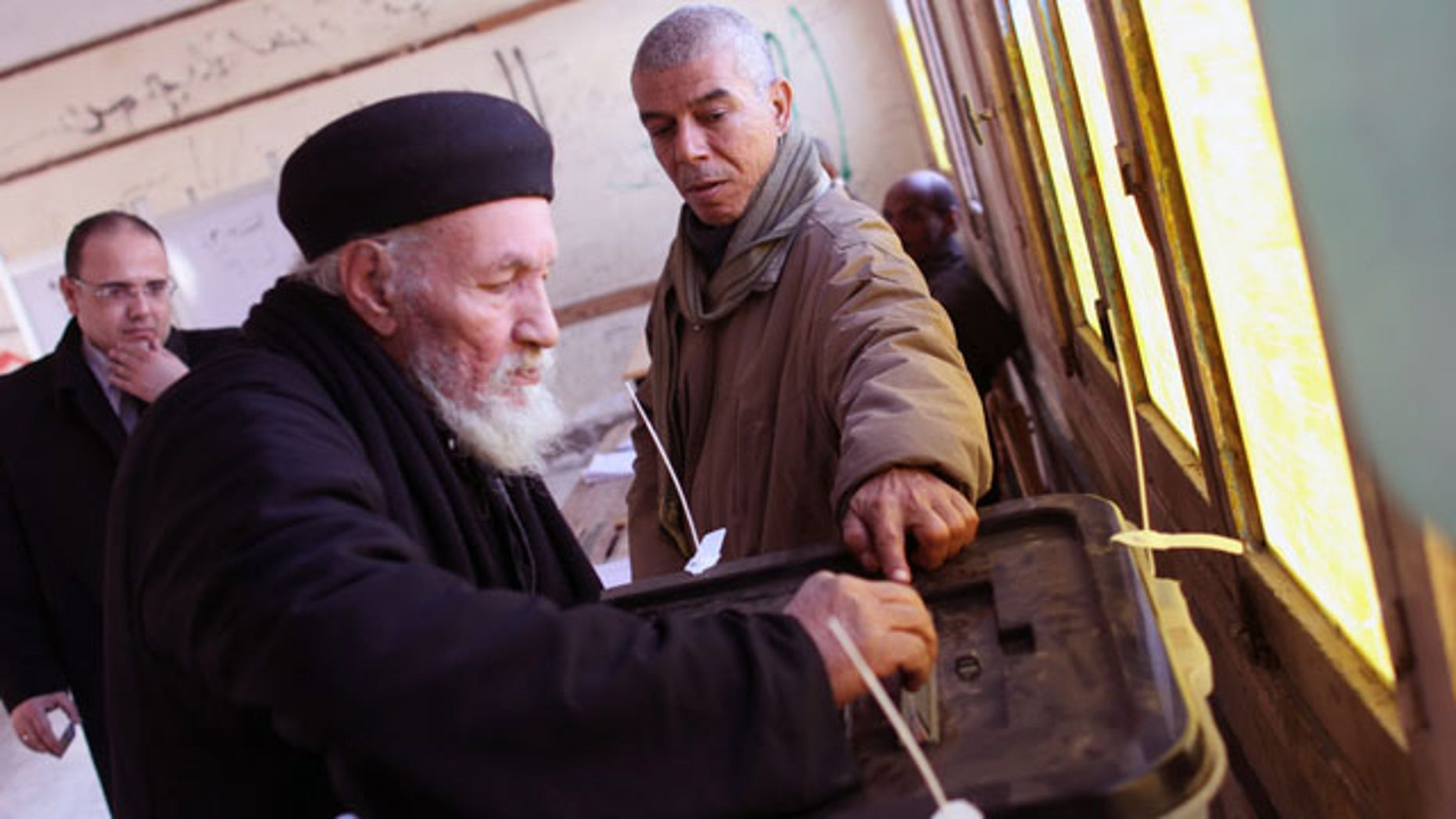 """January 15, 2014: Father Antonious casts his ballot in a constitutional referendum inside a polling station in Dalga village of Minya, Egypt. Father Antonious is one of the priests of the Virgin Mary and St. Abraam Monastery that was looted and burned by supporters of ousted Islamist President Mohammed Morsi in August. Christians are voting """"yes"""" on a new charter that criminalizes discrimination and instructs the next legislature to ease restrictions on building churches. (AP Photo/Roger Anis, El Shorouk Newspaper)"""