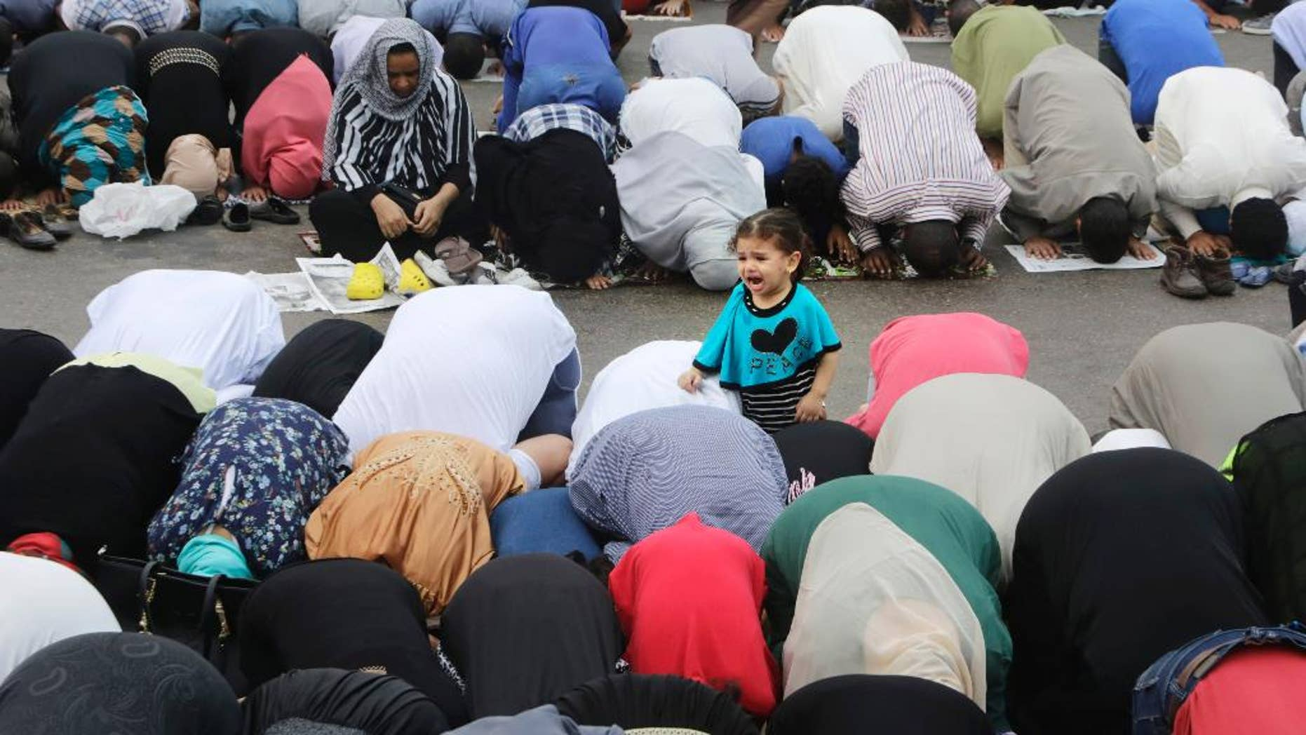 An Egyptian girl cries as her mother joins others offering an Eid al-Fitr prayer, marking the end of the Muslim holy month of Ramadan in Cairo, Egypt, Friday, July 17, 2015. (AP Photo/Amr Nabil)