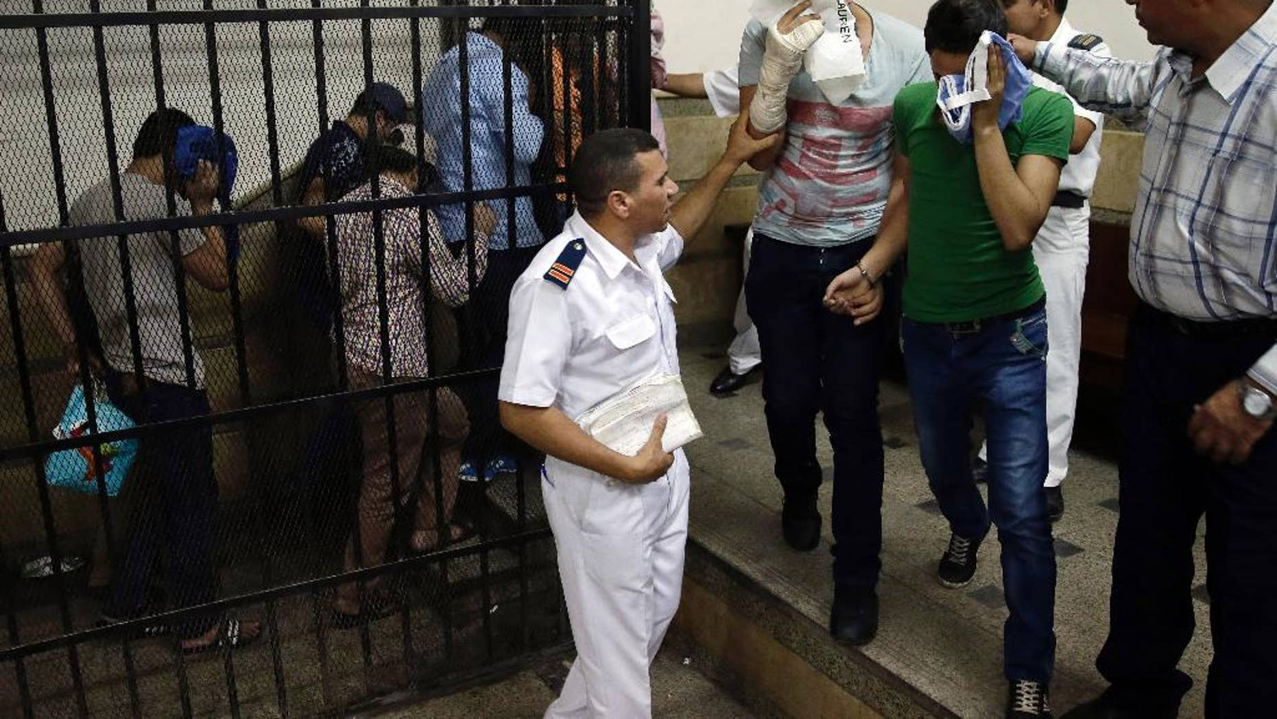"""FILE - In this Saturday, Nov. 1, 2014 file photo, Eight Egyptian men convicted for """"inciting debauchery"""" following their appearance in a video of an alleged same-sex wedding party on a Nile boat leave the defendant's cage in a courtroom in Cairo, Egypt. An Egyptian official says security forces raided a bath house and arrested 25 men for homosexuality, dragging them naked out of the building in downtown Cairo. (AP Photo/Hassan Ammar, File)"""