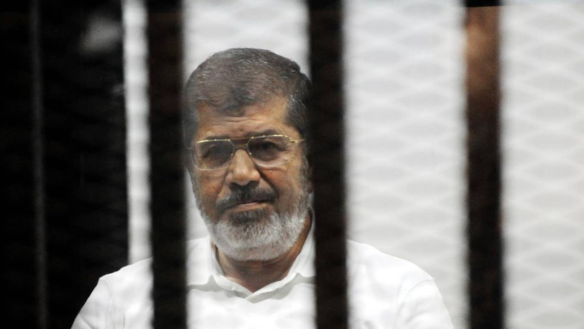FILE - In this file photo taken Monday, Nov. 3, 2014, Egypt's ousted Islamist President Mohammed Morsi sits in the defendant cage in the Police Academy courthouse during a court hearing on charges of inciting the murder of his opponents, in Cairo, Egypt. Egypt's state news agency said prosecutors have asked for the death sentence for Morsi and other Muslim Brotherhood leaders on trial on espionage charges. (AP Photo/Mohammed al-Law, File)