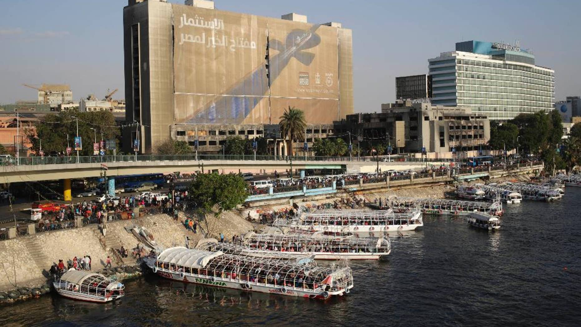 """April 14, 2015: A banner reading, """"Investment is the key to Egypt's welfare,"""" hangs from the former National Democratic Party (NDP) headquarters, which was torched during the 2011 uprising that ousted President Hosni Mubarak, in Cairo."""