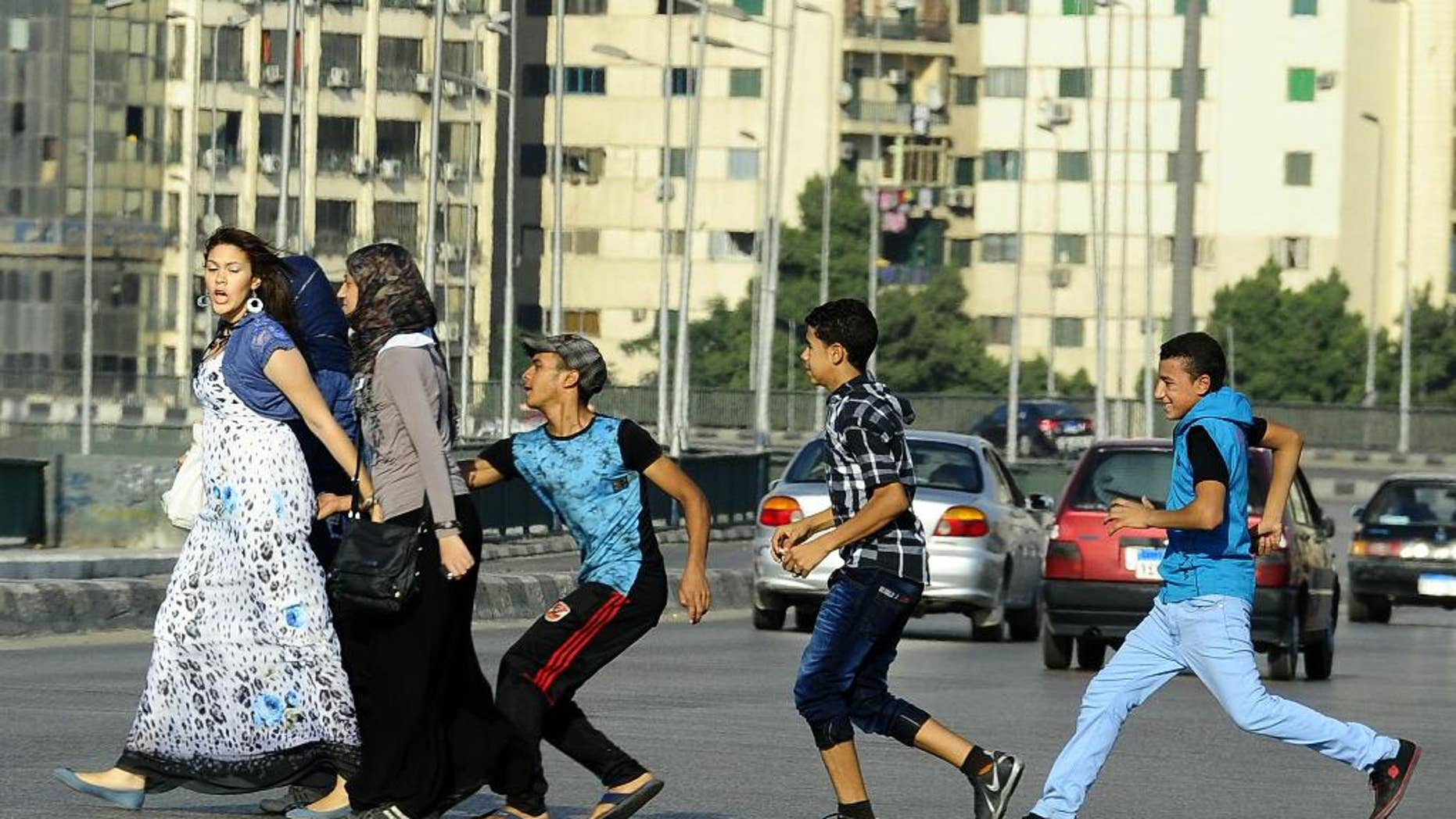 FILE -- In this Monday, Aug. 20, 2012 file photo, an Egyptian youth, trailed by his friends, gropes a woman crossing the street with her friends in Cairo, Egypt. Abdel-Fattah el-Sissi, Egypt's newly sworn-in president, has apologized in person to a woman who was sexually assaulted by a mob during weekend celebrations marking his inauguration. Several women were assaulted during the Sunday, June 8, 2014 inaugural festivities. (AP Photo/Ahmed Abd El Latif, El Shorouk Newspaper, File)   EGYPT OUT