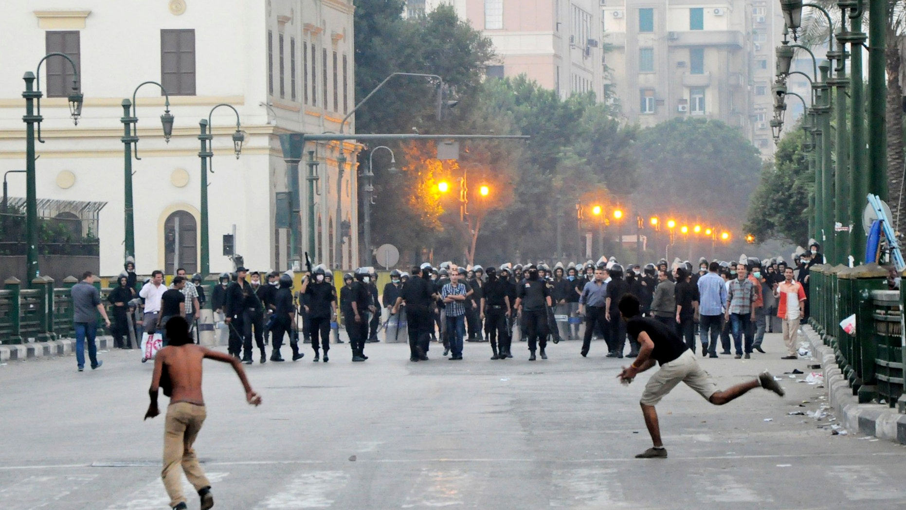 Sept. 15, 2012: Egyptian protesters hurl stones at riot police in downtown Cairo, Egypt, before police cleared the area after days of protests against a film ridiculing the Prophet Muhammad.