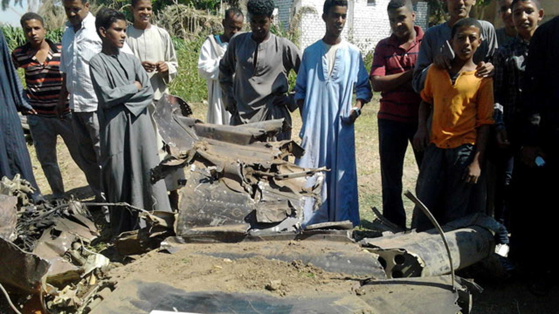 October 13, 2013: Egyptians gather around the remains of a Soviet-made MiG-21 fighter jet belonging to the Egyptian air force that crashed Sunday, while on a training mission near the southern ancient city of Luxor, which officials said killed a villager on the ground and injured several. (AP Photo)