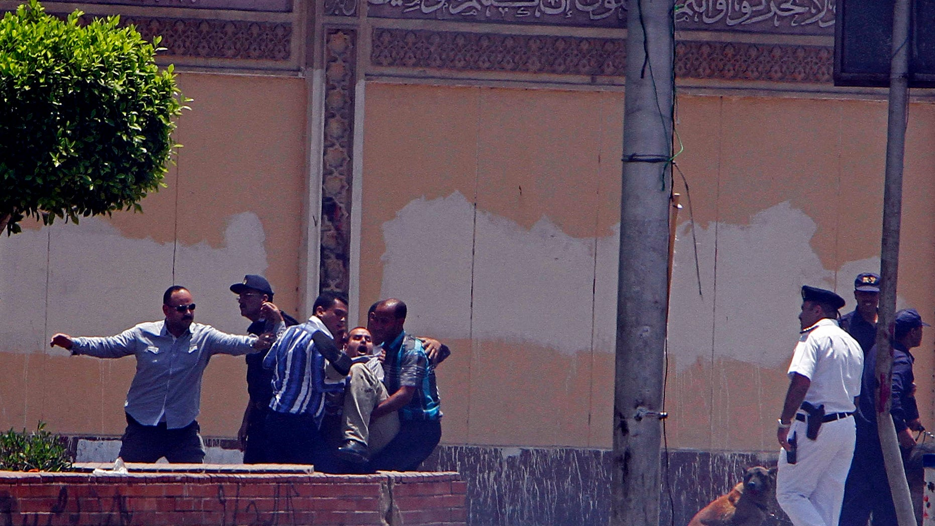 June 30, 2014 - Egyptian security forces and medics help an injured man to an ambulance after 2 homemade bombs went off near the presidential palace in Cairo, Egypt.