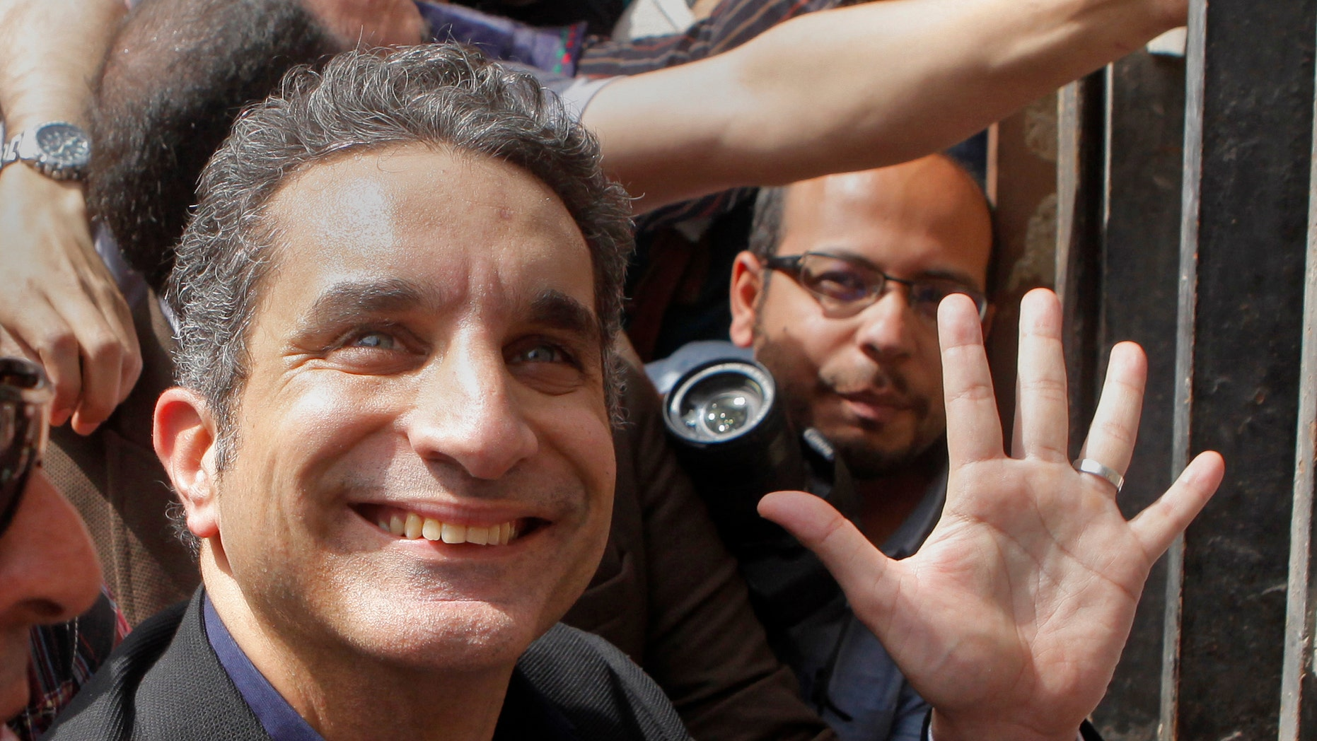Popular Egyptian television satirist Bassem Youssef, who has come to be known as Egypt's Jon Stewart, waves to is supporters as he enters Egypt's state prosecutors office to face accusations of insulting Islam and the country's Islamist leader in Cairo, Egypt, Sunday, March 31, 2013. Government opponents said the warrant against such a high profile figure, known for lampooning President Mohammed Morsi and the new Islamist political class, was an escalation in a campaign to intimidate critics. (AP Photo/Amr Nabil)