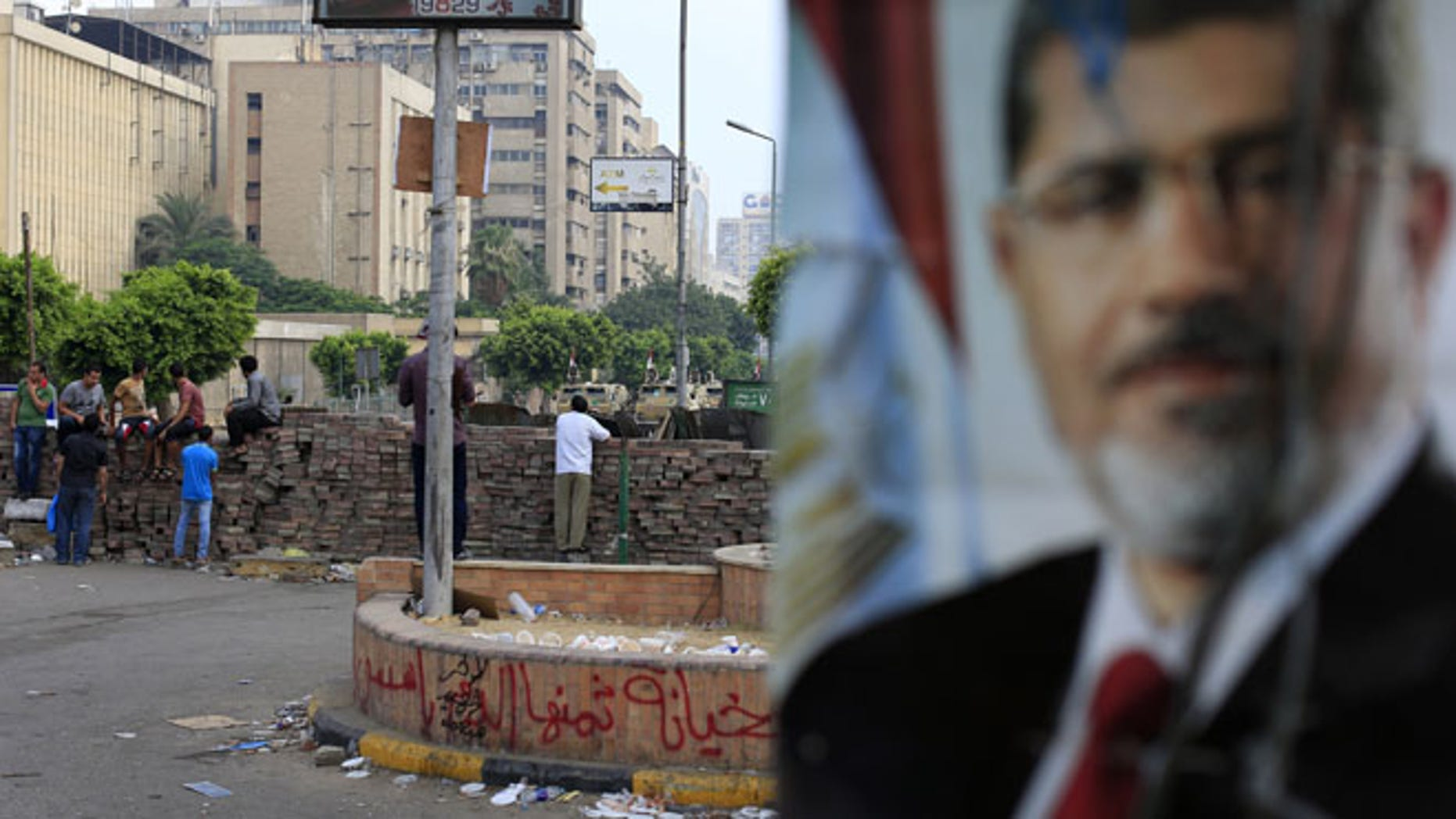 July 10, 2013: Supporters of ousted President Mohammed Morsi protest as army soldiers guard at the Republican Guard building in Nasr City, in Cairo, Egypt.
