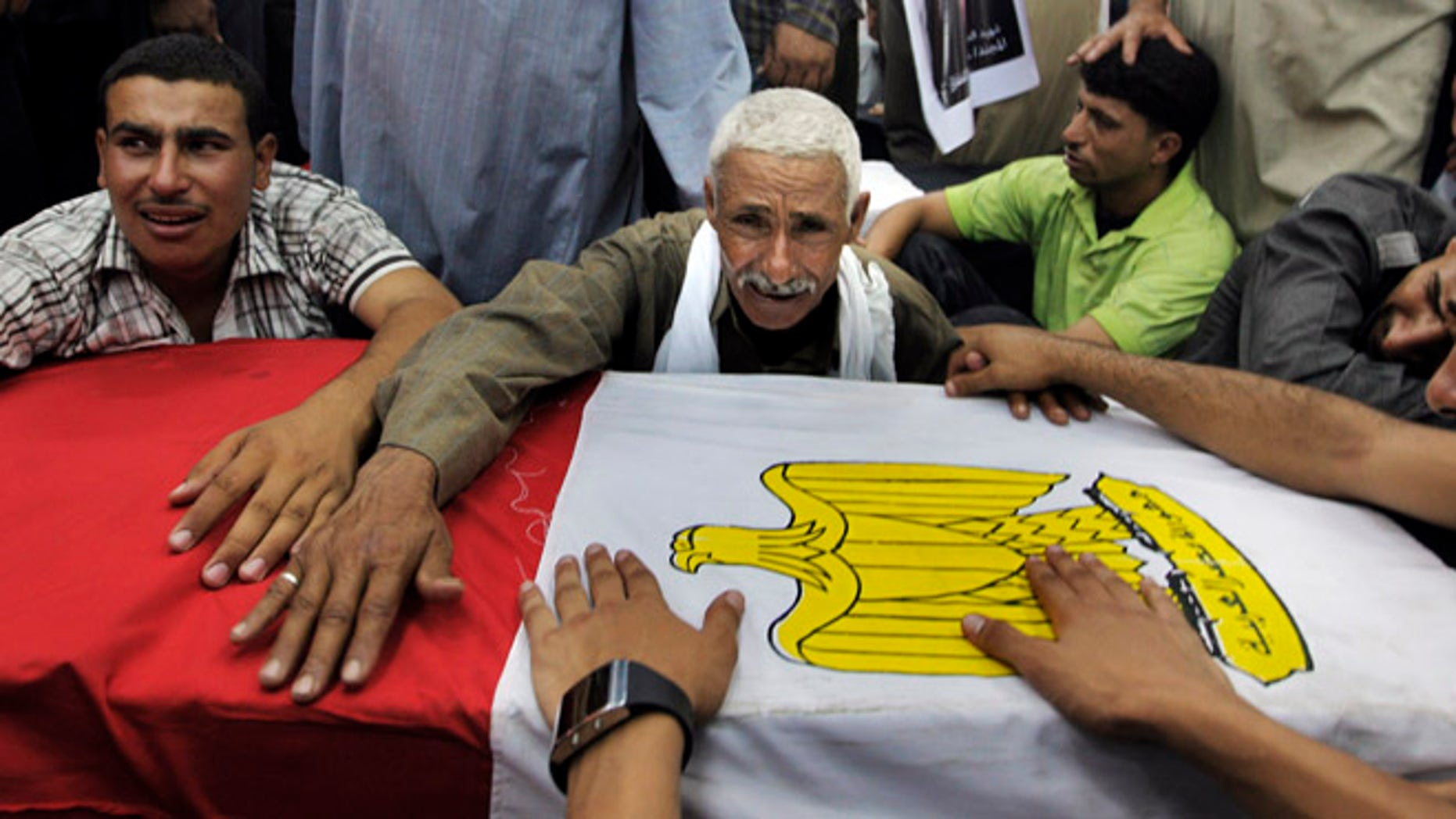 Aug. 7, 2012: Relatives of an Egyptian soldier mourn during the funeral of one of 16 soldiers killed in an attack over the weekend by suspected militants in Sinai in Cairo, Egypt.