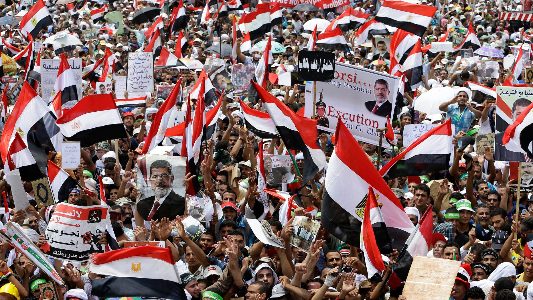 July 19, 2013 - Supporters of Egypt's ousted President Mohammed Morsi wave their national flags during a demonstration where protesters have installed their camp and hold their daily rally, at Nasr City, Cairo, Egypt.