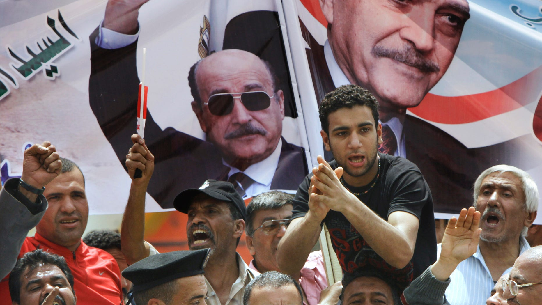 April 8, 2012: Supporters of former Egyptian Vice President Omar Suleiman chant in front of his posters out side the Higher Presidential Elections Commission, in Cairo, Egypt.