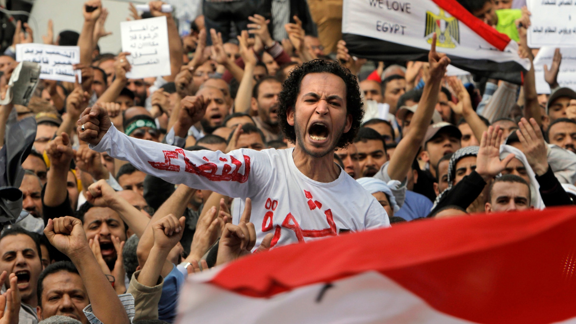 """April 19, 2013 - Egyptian Muslim Brotherhood members shout slogans during a protest in front of the Supreme Judicial Council in Cairo, Egypt. Arabic on the T-shirt reads, """"clean judiciary."""""""