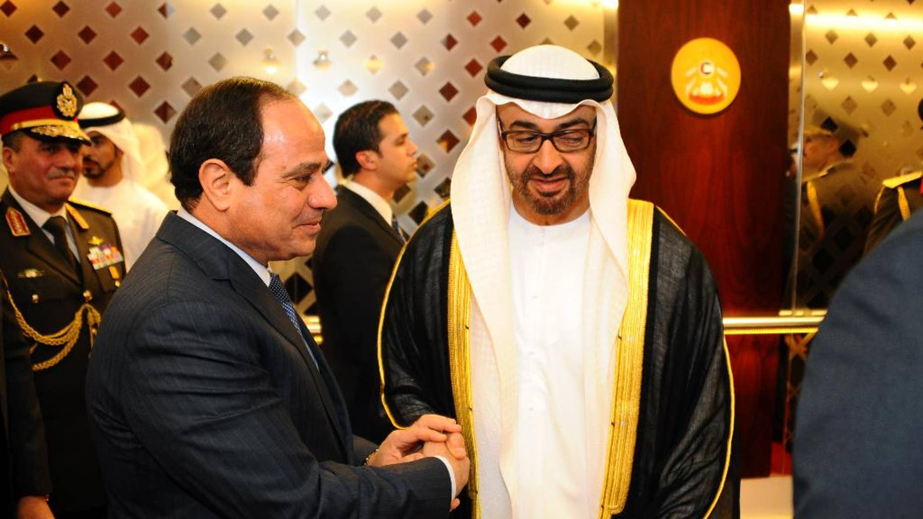 In this Saturday, Jan. 17, 2015 photo, Egyptian President Abdel-Fattah el-Sissi, left, shakes hands with Abu Dhabi crown prince, Sheikh Mohammed bin Zayed Al Nahyan, in Abu Dhabi, United Arab Emirates. The first official visit by El-Sissi reflects the strong support the Emirates has given el-Sissi's government since he was elected in June after leading the 2013 military overthrow of Islamist President Mohammed Morsi. (AP Photo/MENA)