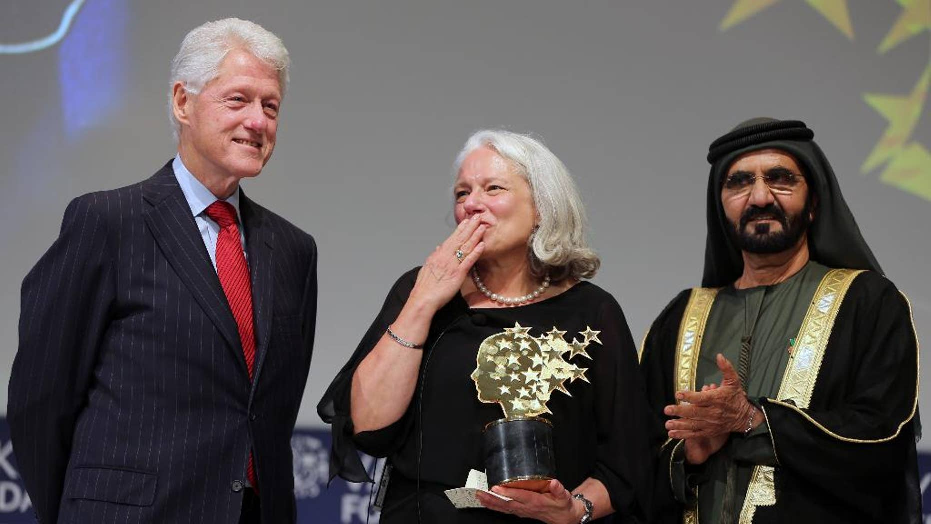 Nancie Atwell, a teacher from Southport, Maine, U.S., center, throws a kiss as she poses with former President of the United States Bill Clinton, left, and Sheikh Mohammed bin Rashid Al Maktoum, prime minister of the U.A.E. and Ruler of Dubai, after she won the $1 million Global Teacher Prize in Dubai, United Arab Emirates, Sunday, March 15, 2015. Atwell has been teaching since 1973 and founded the Center for Teaching and Learning in Southport. (AP Photo/Kamran Jebreili)