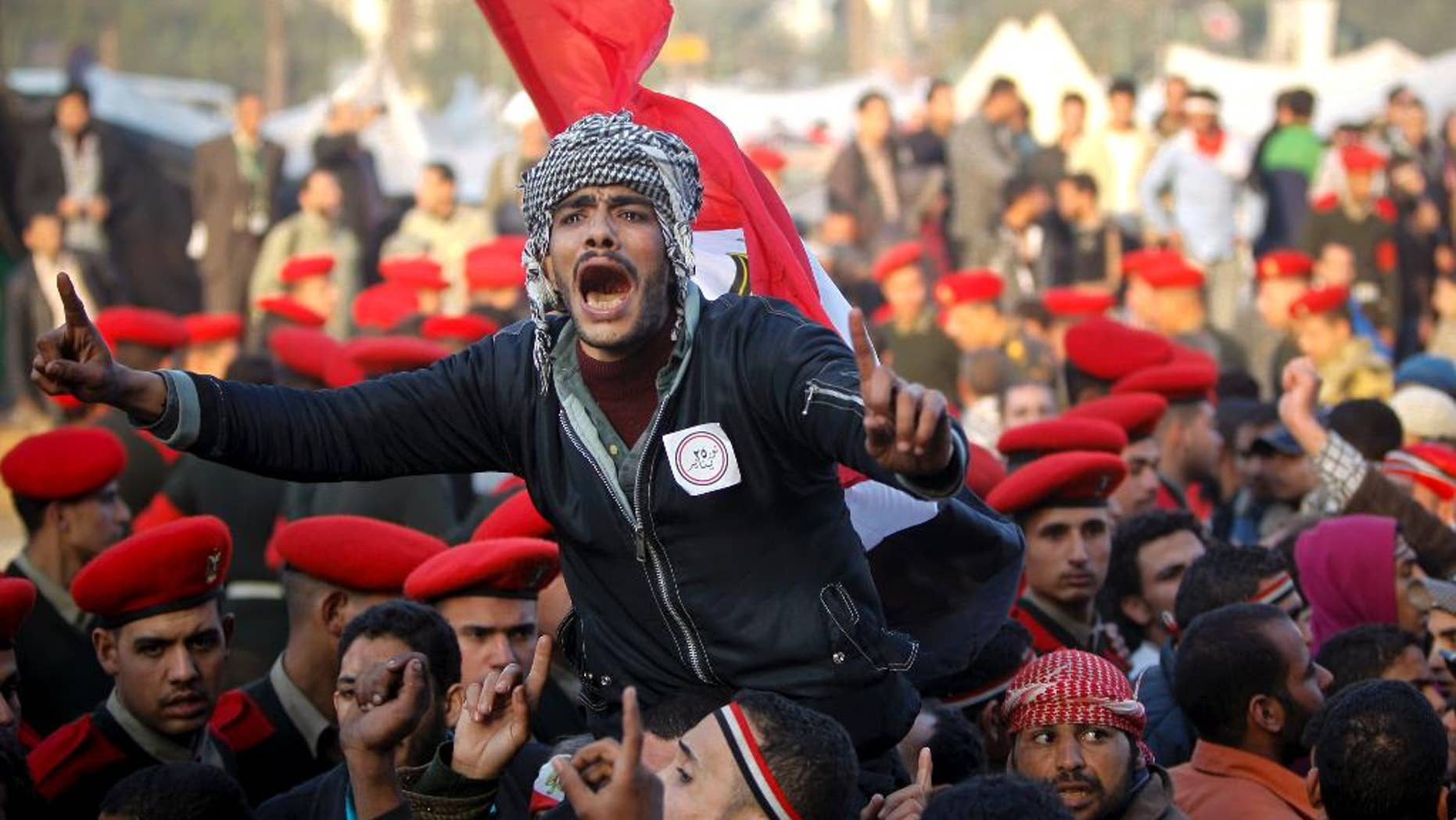 FILE - In this Feb. 13, 2011 file photo, remaining Egyptian protesters shout slogans as they are surrounded by army soldiers trying to lead them away from Tahrir Square in Cairo, Egypt. Within days, a cheering world community was riveted to screens as Egypt's long-submissive people thronged to Cairo's Tahrir Square, braving bullets and refusing to leave until veteran ruler Hosni Mubarak stepped down. (AP Photo/Tara Todras-Whitehill, File)