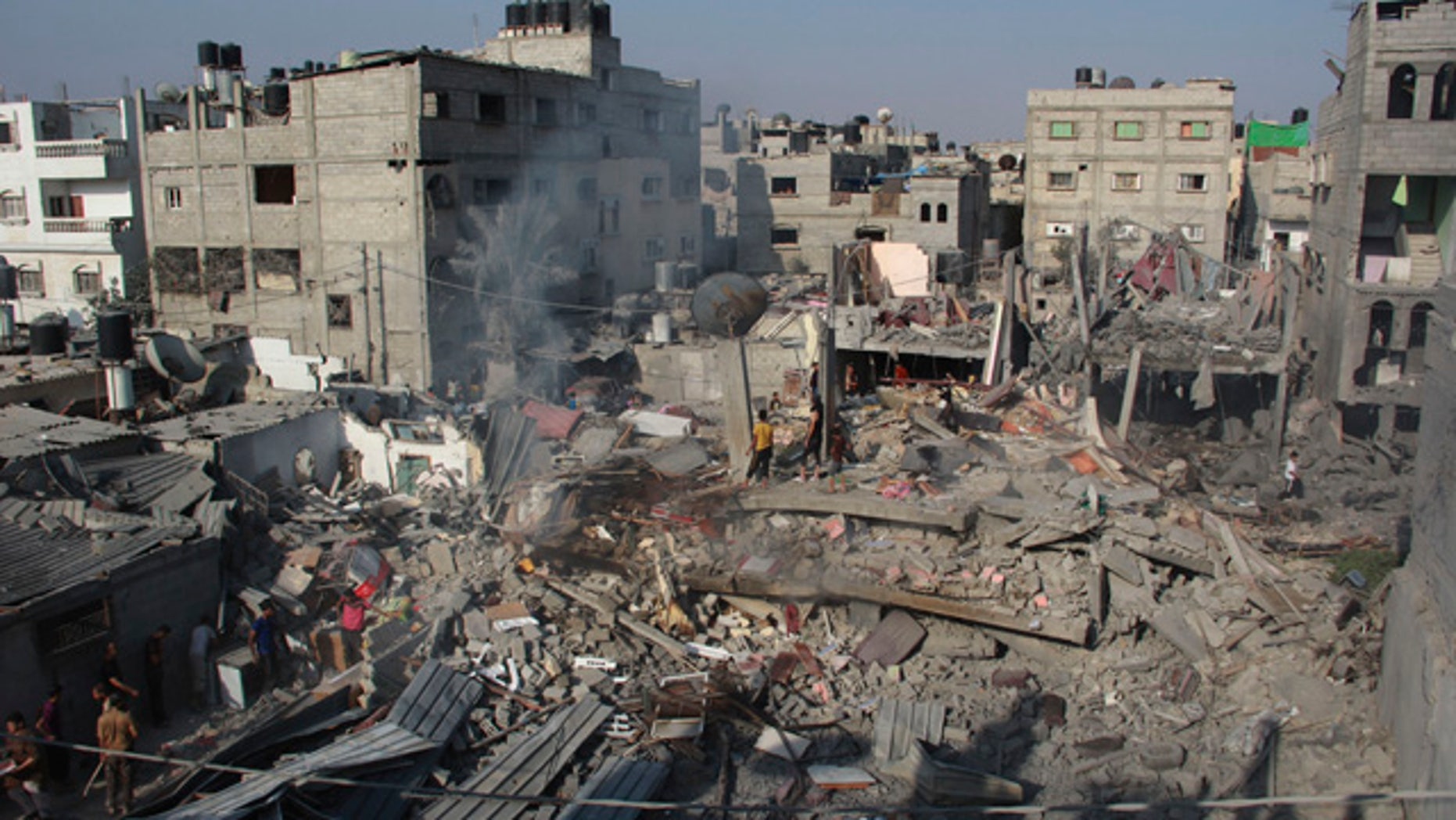 FILE - In this Saturday, Aug. 2, 2014 file photo, Palestinians stand on the rubble of houses destroyed in an Israeli strike in Rafah, southern Gaza Strip.  (AP Photo/Hatem Ali, File)