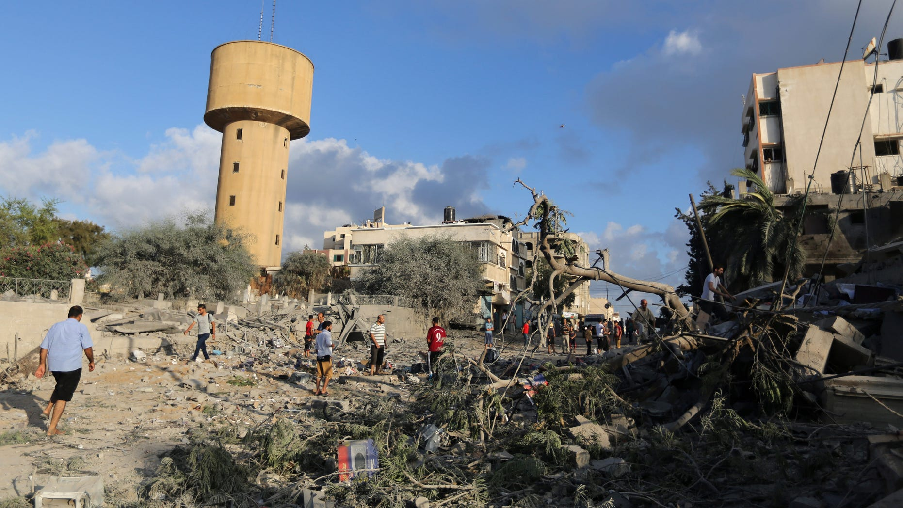July 25, 2014 - Palestinians walk on the rubble of buildings damaged in an Israeli airstrike in Gaza City,