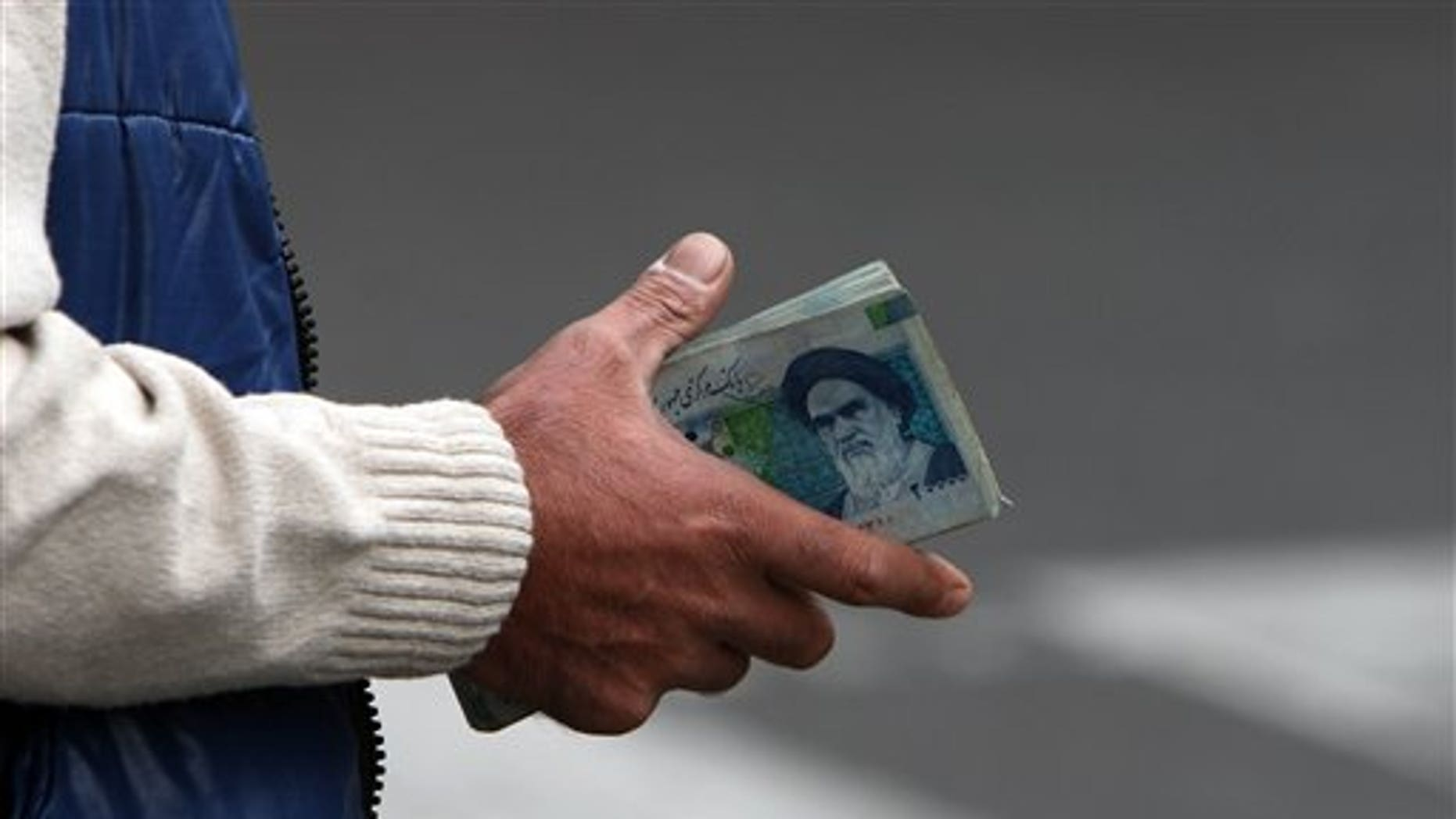 Oct. 30, 2008: In this file photo, an Iranian money changer holds currency with Ayatollah Ruhollah Khomeini's image in Tehran, Iran.