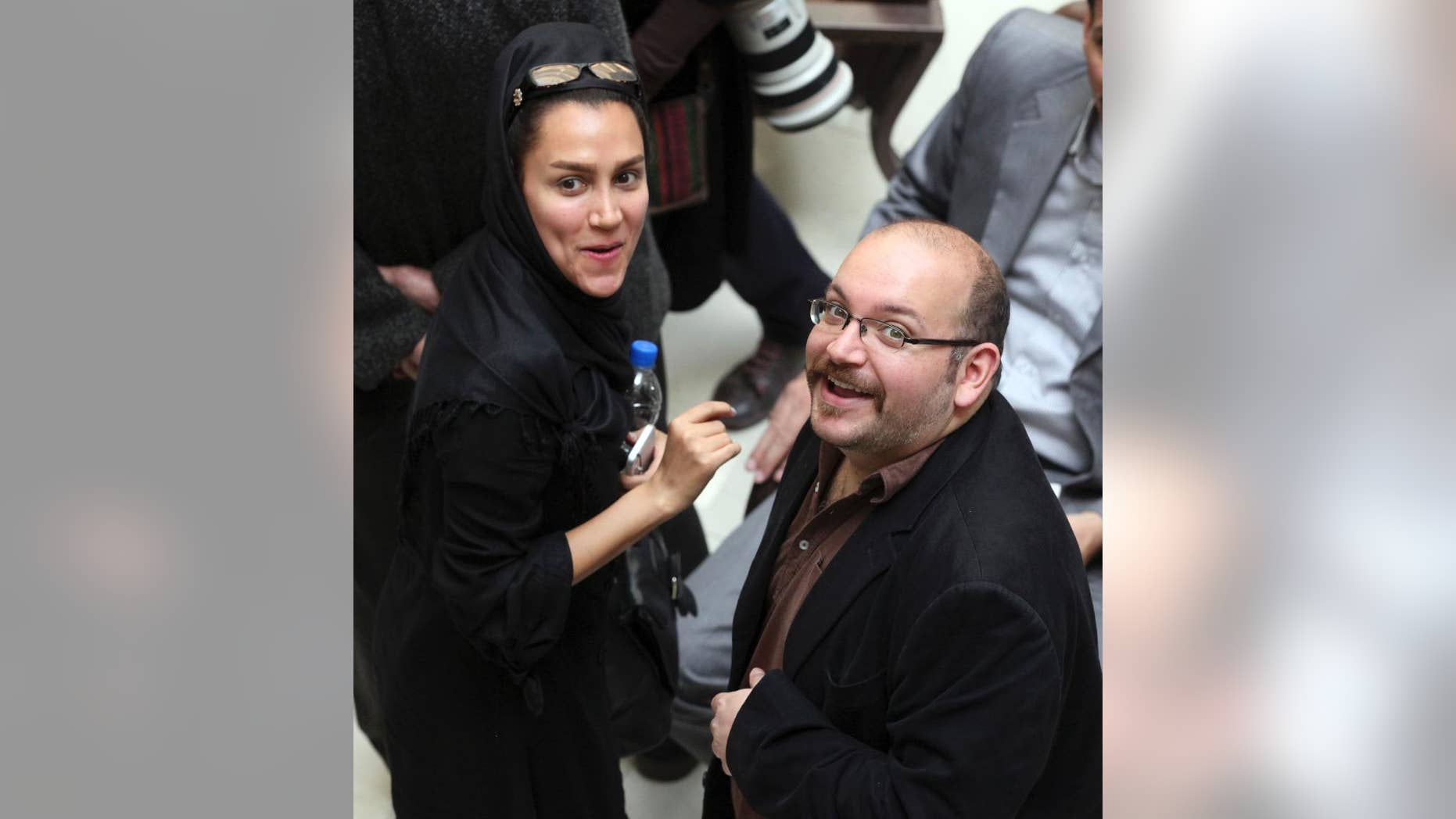 In this photo taken on April 11, 2013, Jason Rezaian, right, an Iranian-American correspondent for the Washington Post, and his wife Yeganeh Salehi, an Iranian correspondent for the Abu Dhabi-based daily newspaper The National, smile as they attend a presidential campaign of President Hassan Rouhani in Tehran, Iran. They have been held in custody for a month since their detention July 2014 in Iran, suggesting a possible struggle between a new guard of moderates pushing for greater freedom and the old hard-line establishment. (AP Photo/Vahid Salemi)
