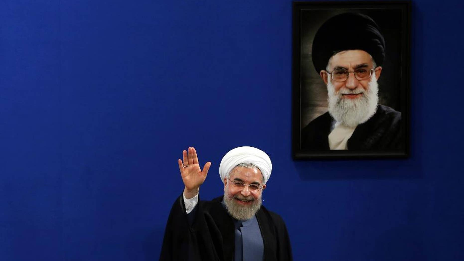 """June 13, 2015: Iran's President Hassan Rouhani waves to reporters at the conclusion of his press conference on the second anniversary of his election, in Tehran, Iran. Rouhani said a final nuclear deal is """"within reach"""" as Iran and world powers face a June 30 deadline for an agreement. A picture of the supreme leader Ayatollah Ali Khamenei hangs on the wall."""