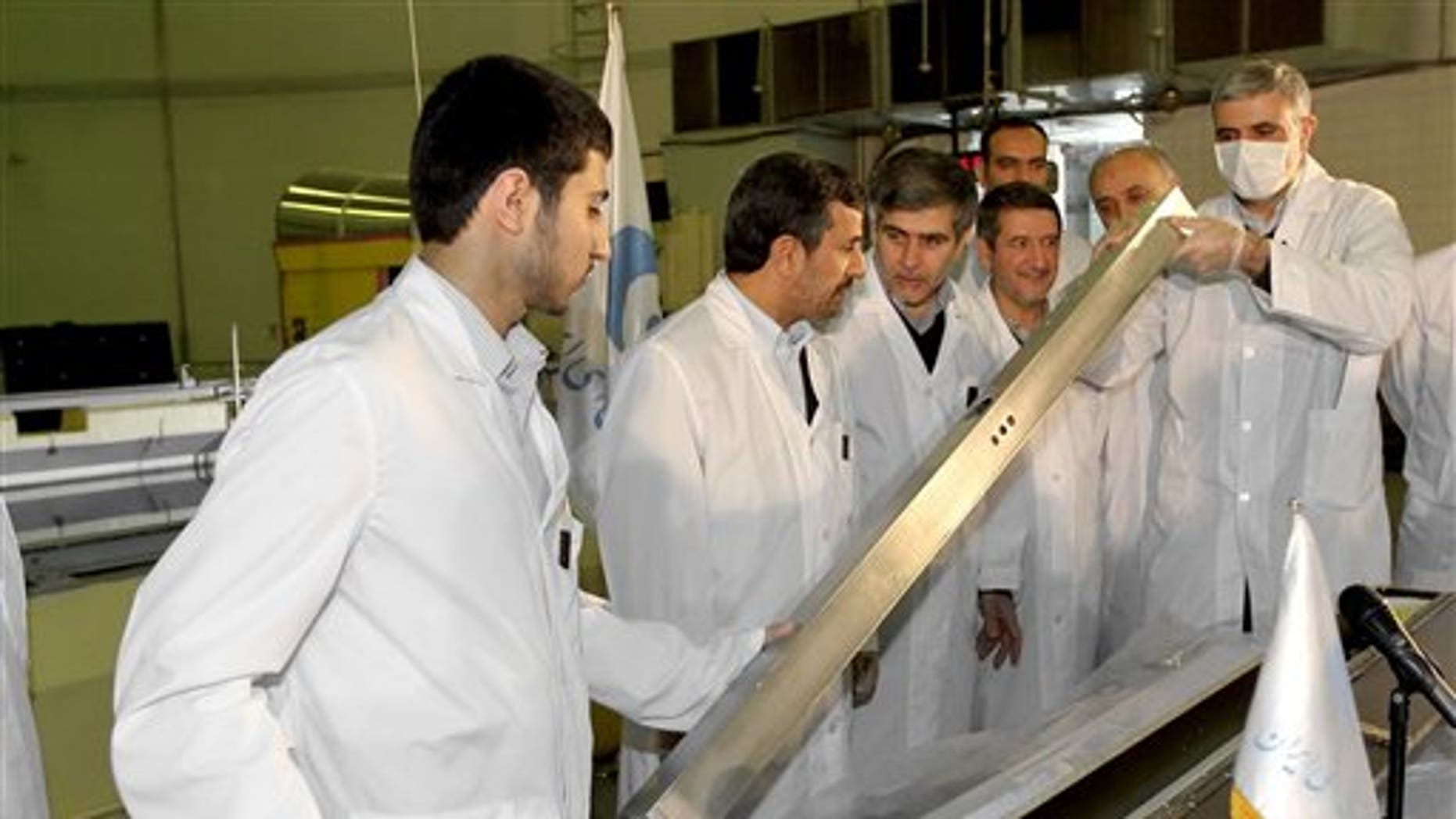 Feb. 15: This photo released by the Iranian President's Office, claims to show Iranian President Mahmoud Ahmadinejad, second left being escorted by technicians during a tour of Tehran's research reactor center in northern Tehran, Iran.