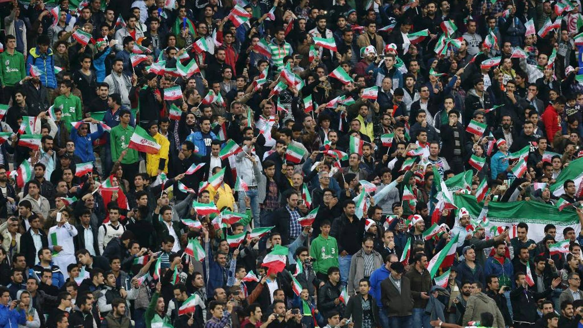 """FILE - In this Nov. 18, 2014 file photo, Iranian soccer supporters wave their country's flag while following a friendly match between Iran and South Korea at the Azadi, (freedom) stadium in Tehran, Iran. Iranian authorities have partially lifted a ban on women attending men's sports matches, a senior sports official said Saturday, April 4, 2015. The announcement comes after FIFA President Sepp Blatter urged Iran last month to end the """"intolerable"""" ban on women watching football in stadiums. (AP Photo/Vahid Salemi, File)"""