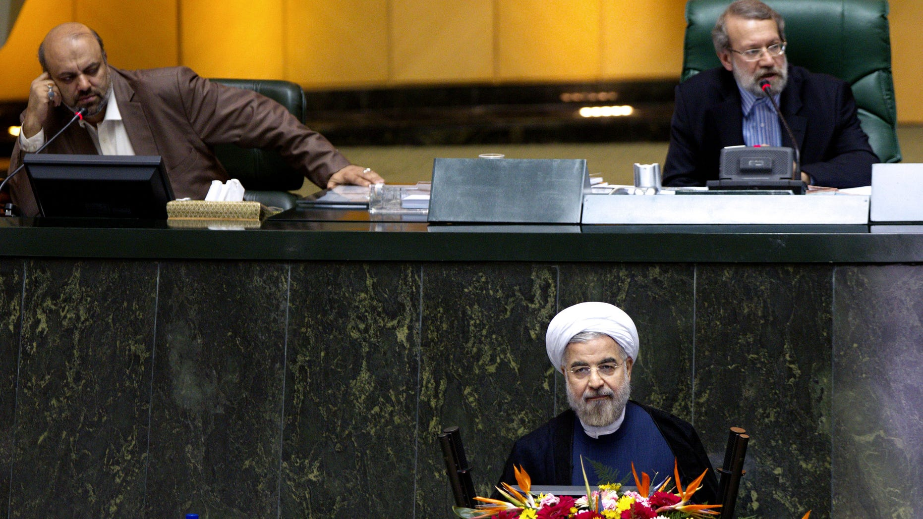 Iranian President Hasan Rouhani, bottom, listens during a parliament session to defend the nominees for the three remaining ministries of his cabinet while parliament speaker Ali Larijani speaks, top right, in Tehran, Iran, Sunday, Oct. 27, 2013. Irans parliament has rejected a close ally of Rouhani for a ministerial post. In a vote Sunday, 141 out of 261 lawmakers present voted against Reza Salehi Amiri, who Rouhani nominated as sports and youth minister. (AP Photo)