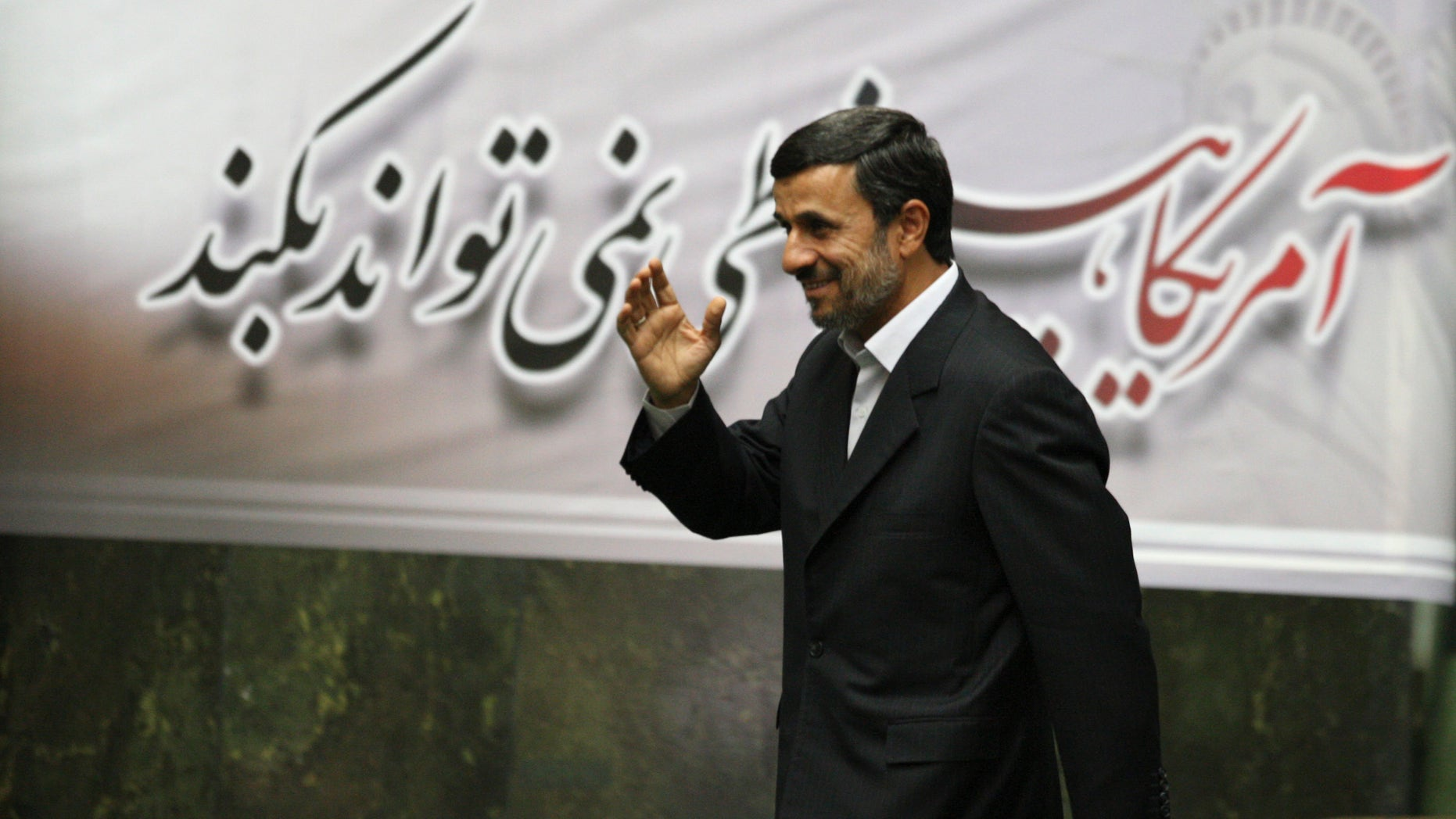 """Nov. 2, 2011: Iranian President Mahmoud Ahmadinejad, waves, as he arrives to attend an open session of parliament for impeachment of his Economy Minister, Shamsoddin Hosseini, unseen, as a banner hangs behind him with a quotation of late revolutionary founder Ayatollah Khomeini, which says """"US can not do anything"""", in Tehran, Iran."""