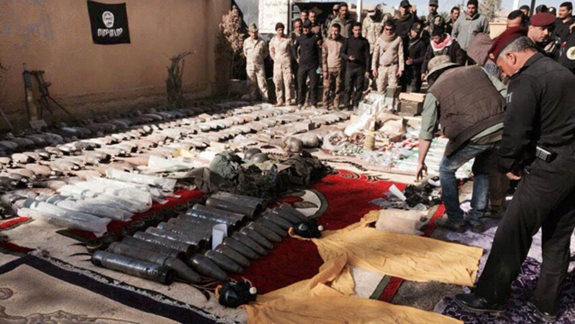 Dec. 10, 2015: Iraqi security forces look at confiscated ISIS weapons and ammunition after regaining control over the last week, in Ramadi, Anbar province, 70 miles west of Baghdad. (AP Photo/Osama Sami)