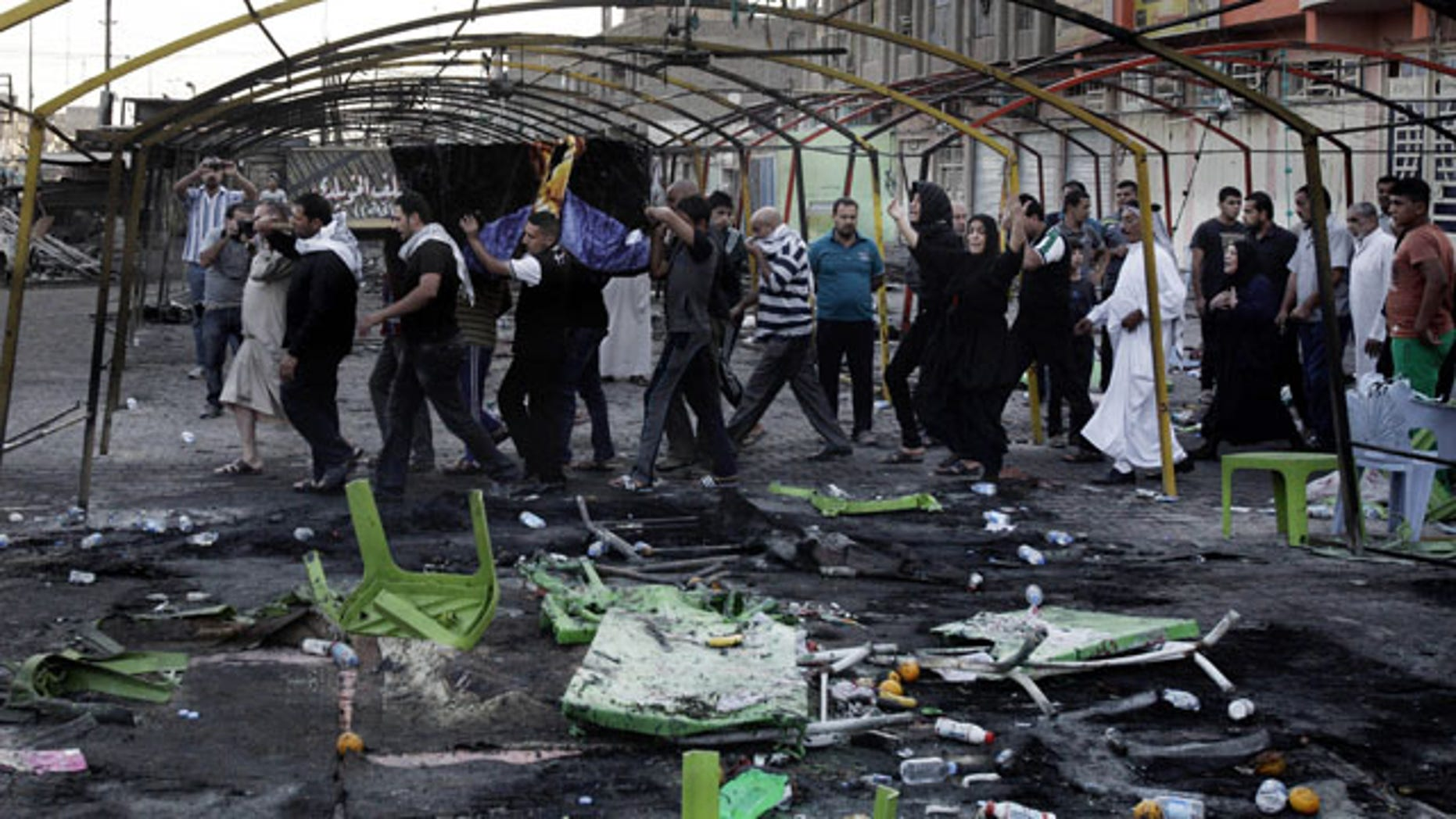 FILE - In this Sept. 22, 2013 file photo, mourners carry the coffin of a man killed on Saturday from a double suicide bomb attack in the Shiite neighborhood of Sadr city in Baghdad, Iraq. (AP Photo)