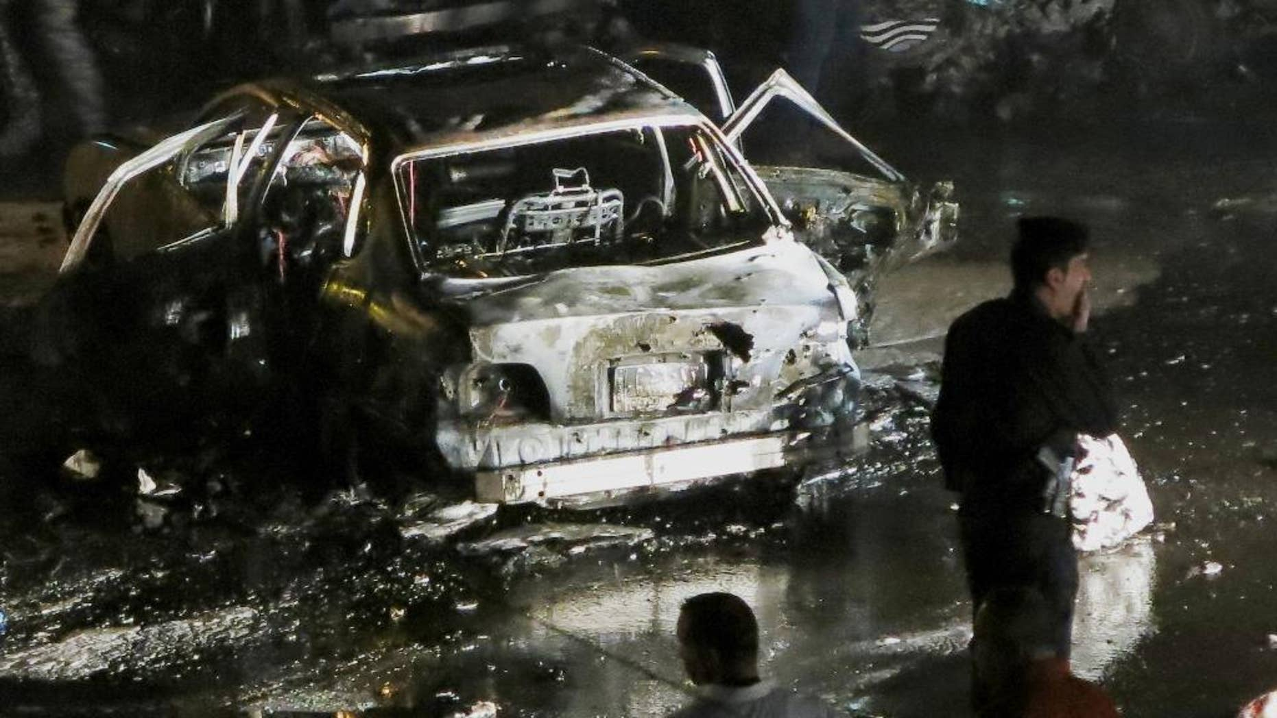 Civilians and security forces gather at the scene of a car bomb explosion in Baghdad's western district of Mansour, Iraq, Monday, April 27, 2015. A series of car bombings targeting busy commercial areas in Iraq's capital left many civilians killed and others wounded, officials said. (AP Photo)