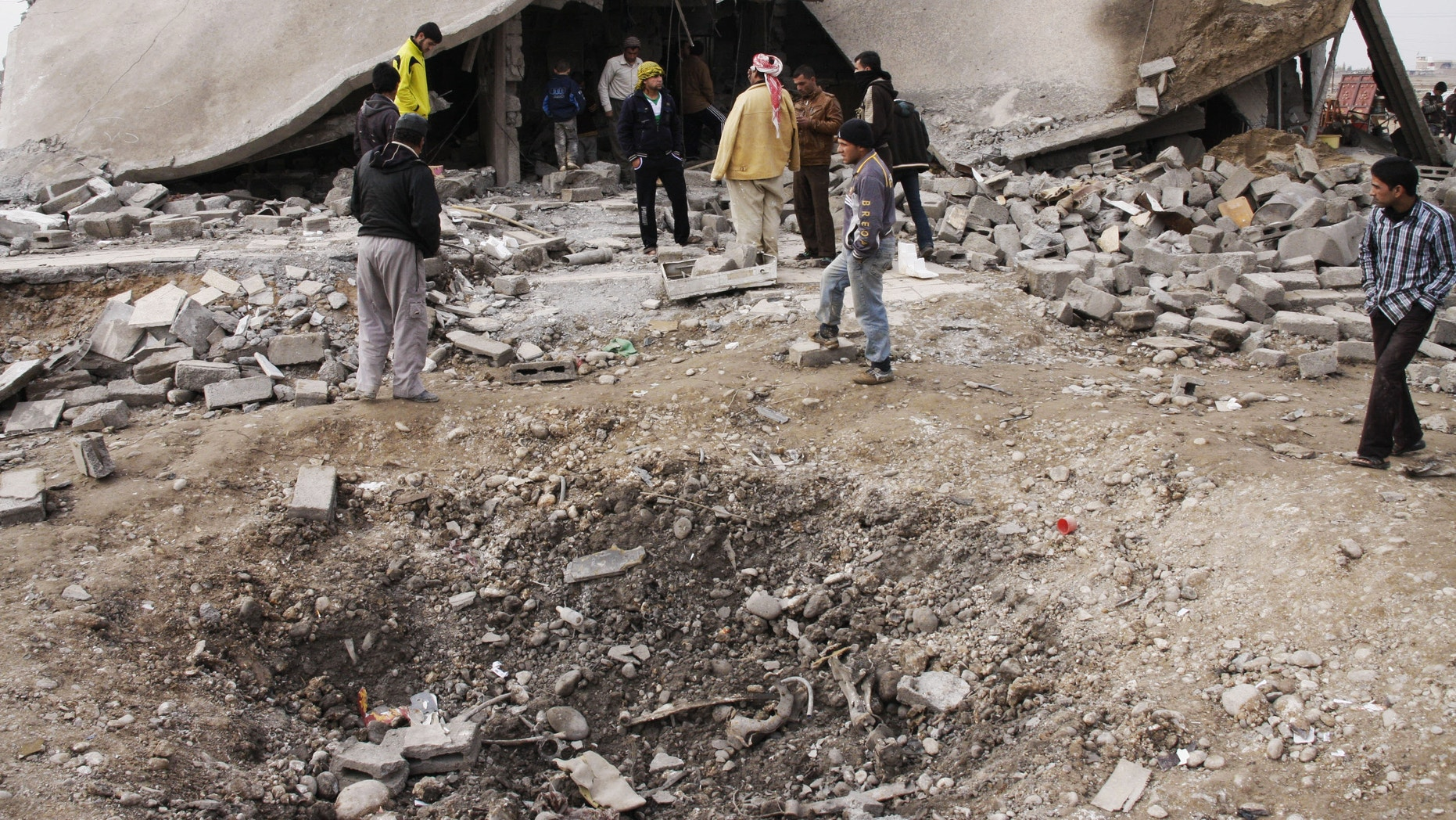 Dec. 17, 2012 - People inspect scene of a car bomb attack in al-Mouafaqiyah, a village inhabited by families from the Shabak ethnic group, near the city of Mosul, northwest of Baghdad.