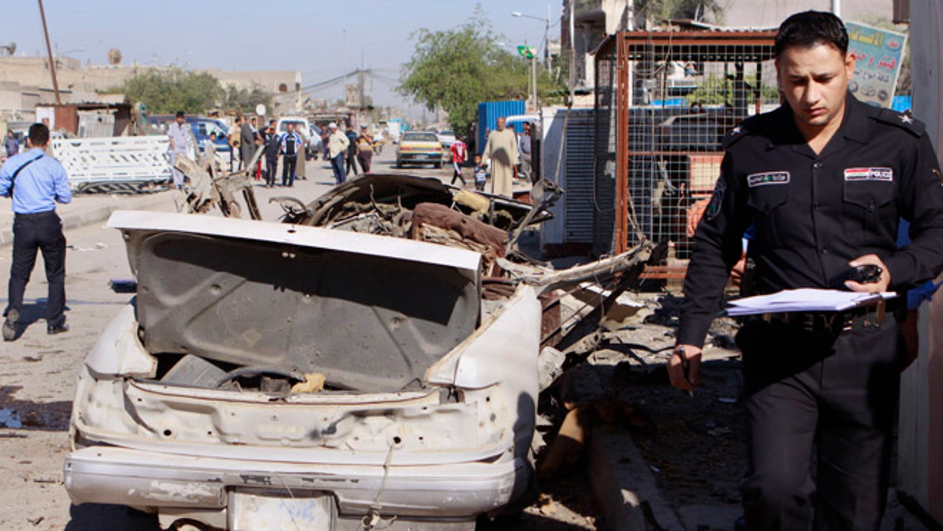 March 19, 2013: A policeman inspects the scene of a car bomb attack in the Shiite stronghold of Sadr City, Baghdad, Iraq.