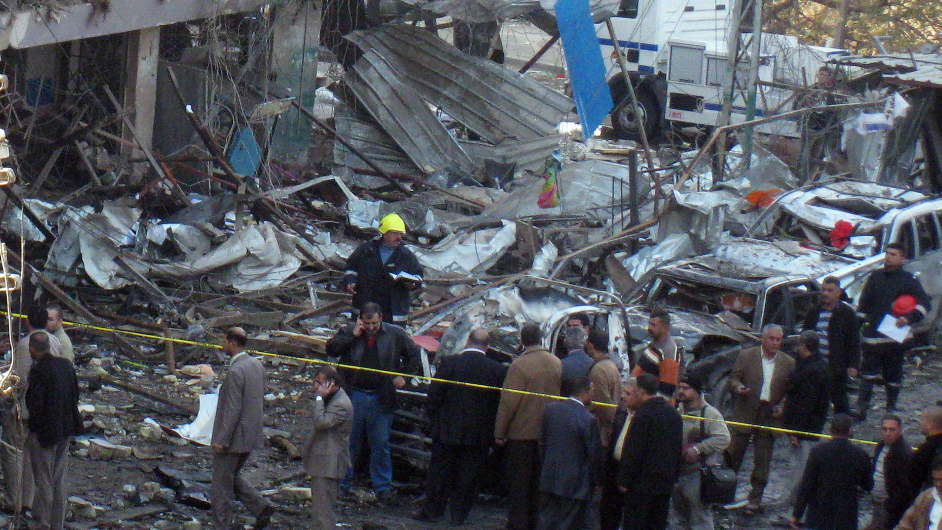 Dec. 22, 2011: Iraqi security forces and people inspect the scene of a car bomb attack in Baghdad, Iraq. A series of blasts Thursday morning in Baghdad killing and wounding scores of people in a coordinated attack designed to wreak havoc across the Iraqi capital.
