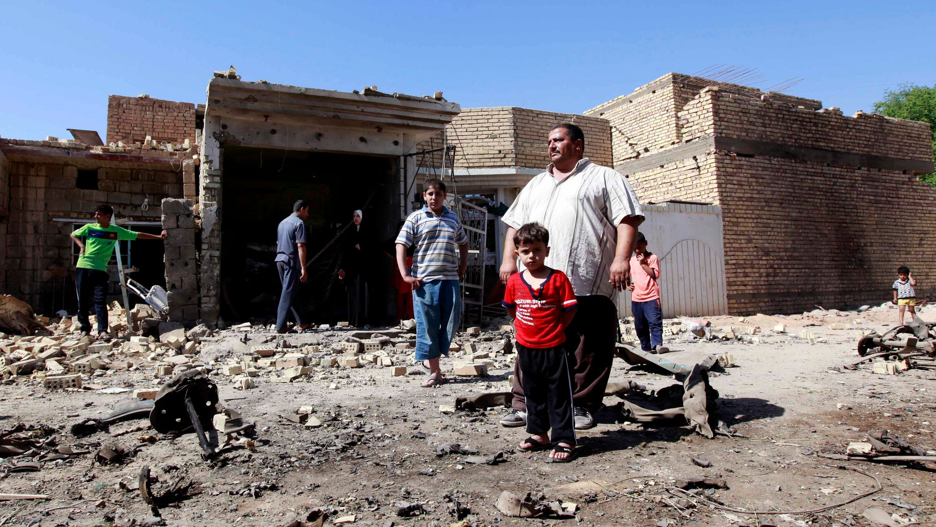 Sept. 30, 2012 - Iraqis stand in rubble at the scene of a car bomb attack in the town of Taji, about 12 miles north of Baghdad, Iraq.