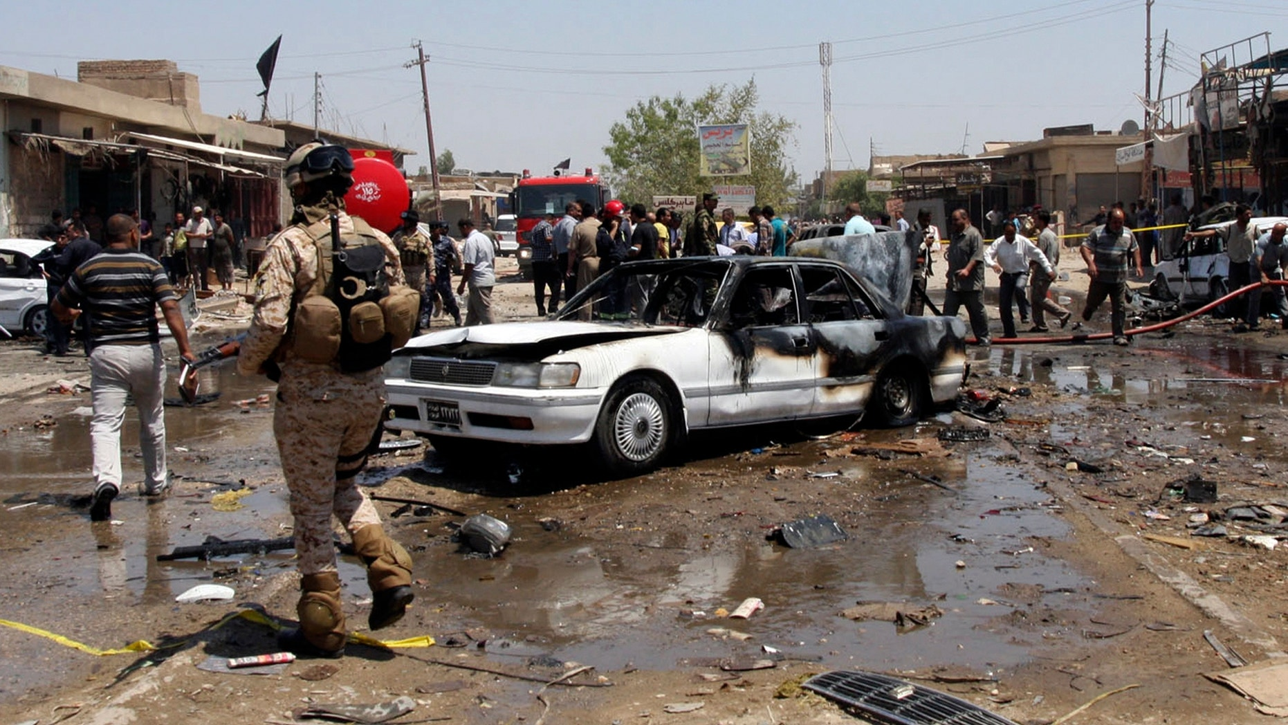 April. 29, 2013 - Civilians and security forces gather at the scene of a car bomb attack in the southern Shiite city of Karbala, south of Baghdad, Iraq.