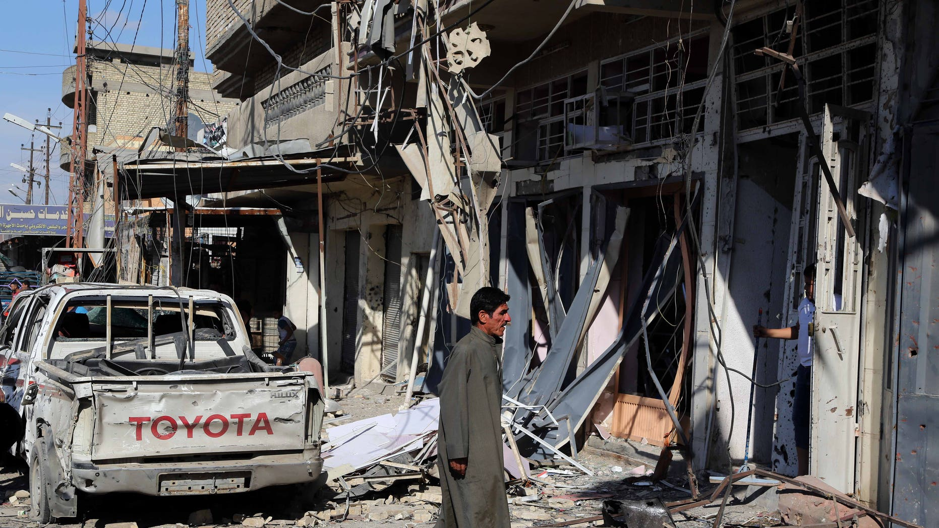 March 23, 2015 - A man inspects the site of a car bomb explosion in a busy commercial street at the Habibiya section of Baghdad's Sadr City, Iraq. Multiple bombings in the Iraqi capital killed and wounded many, Iraqi officials said.