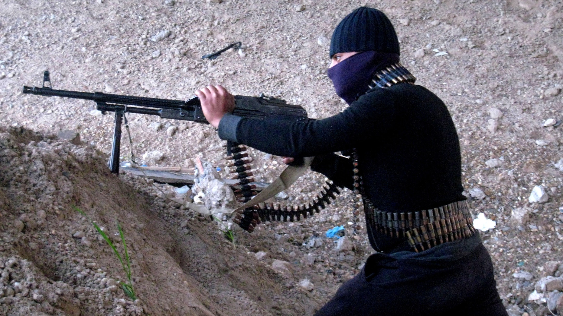 Jan. 19, 2014 - A gunmen takes cover during clashes with Iraqi security forces outside Fallujah, 40 miles west of Baghdad, Iraq.