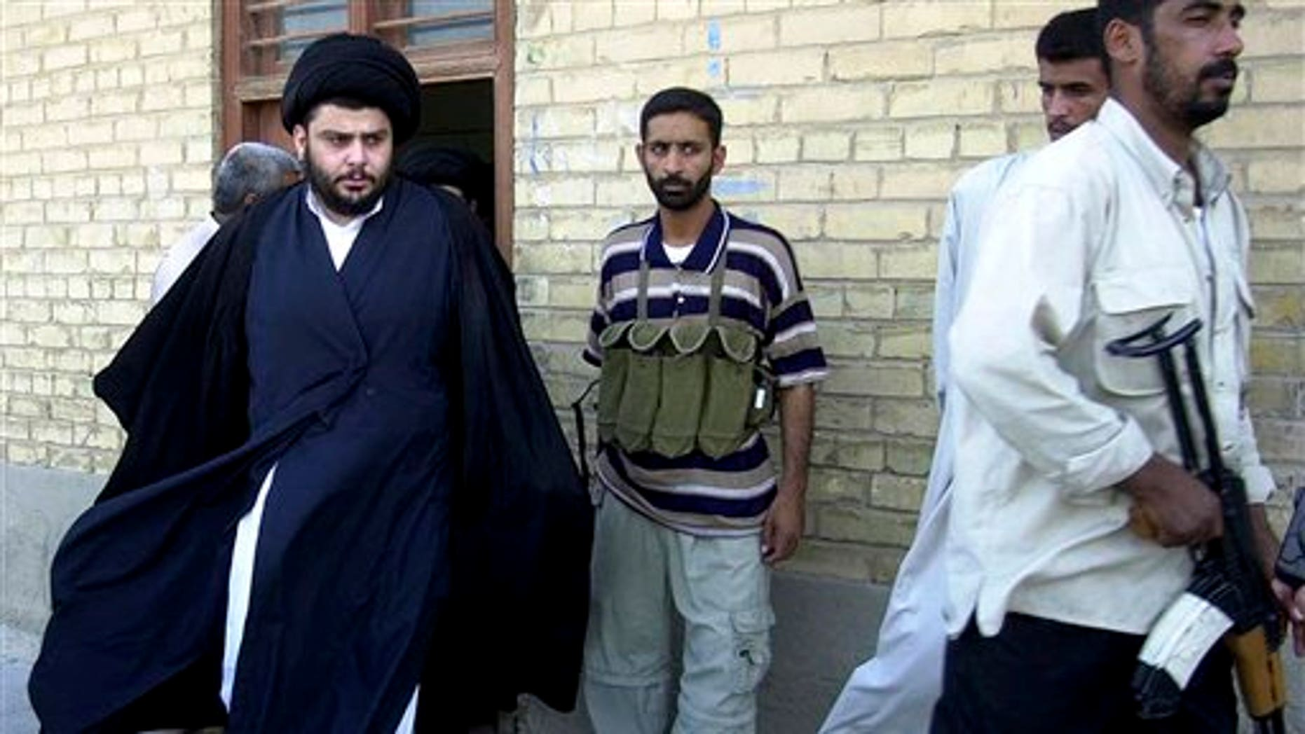 June 5, 2004: Shiite cleric Muqtada al-Sadr, left, steps from an office building in Najaf, Iraq.