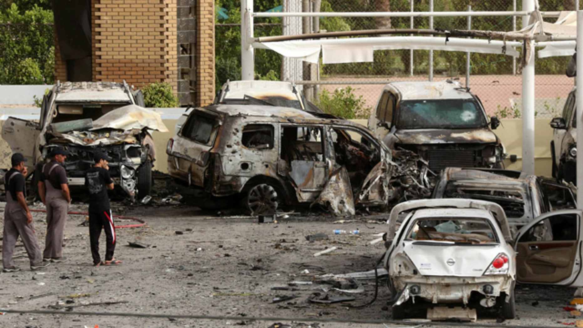 May 29, 2015: Civilians and security forces inspect the aftermath of a car bomb attack in the parking lot of Babil hotel in Karrada neighborhood, Baghdad, Iraq. (AP Photo/Hadi Mizban)