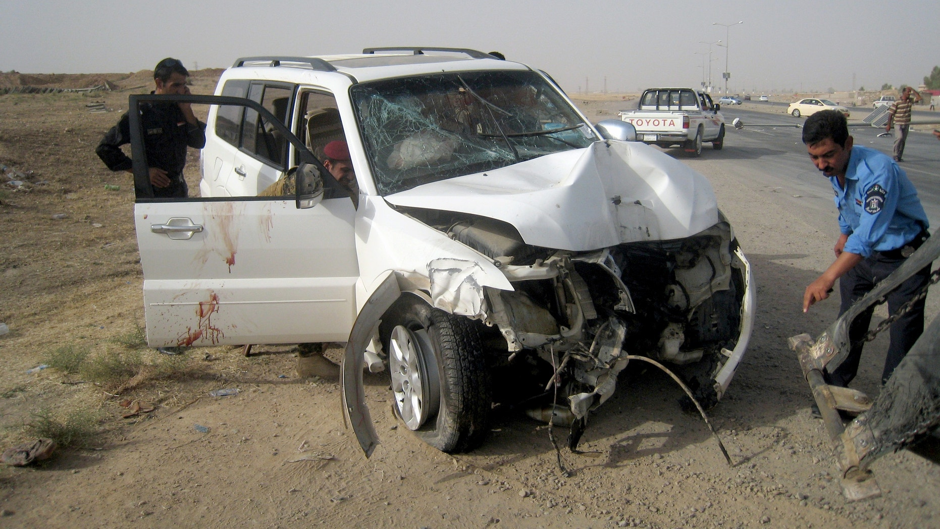 July 22, 2013 - Iraqi policemen prepare to tow away a damaged sport utility vehicle following a drive-by shooting in Kirkuk, north of Baghdad, Iraq.