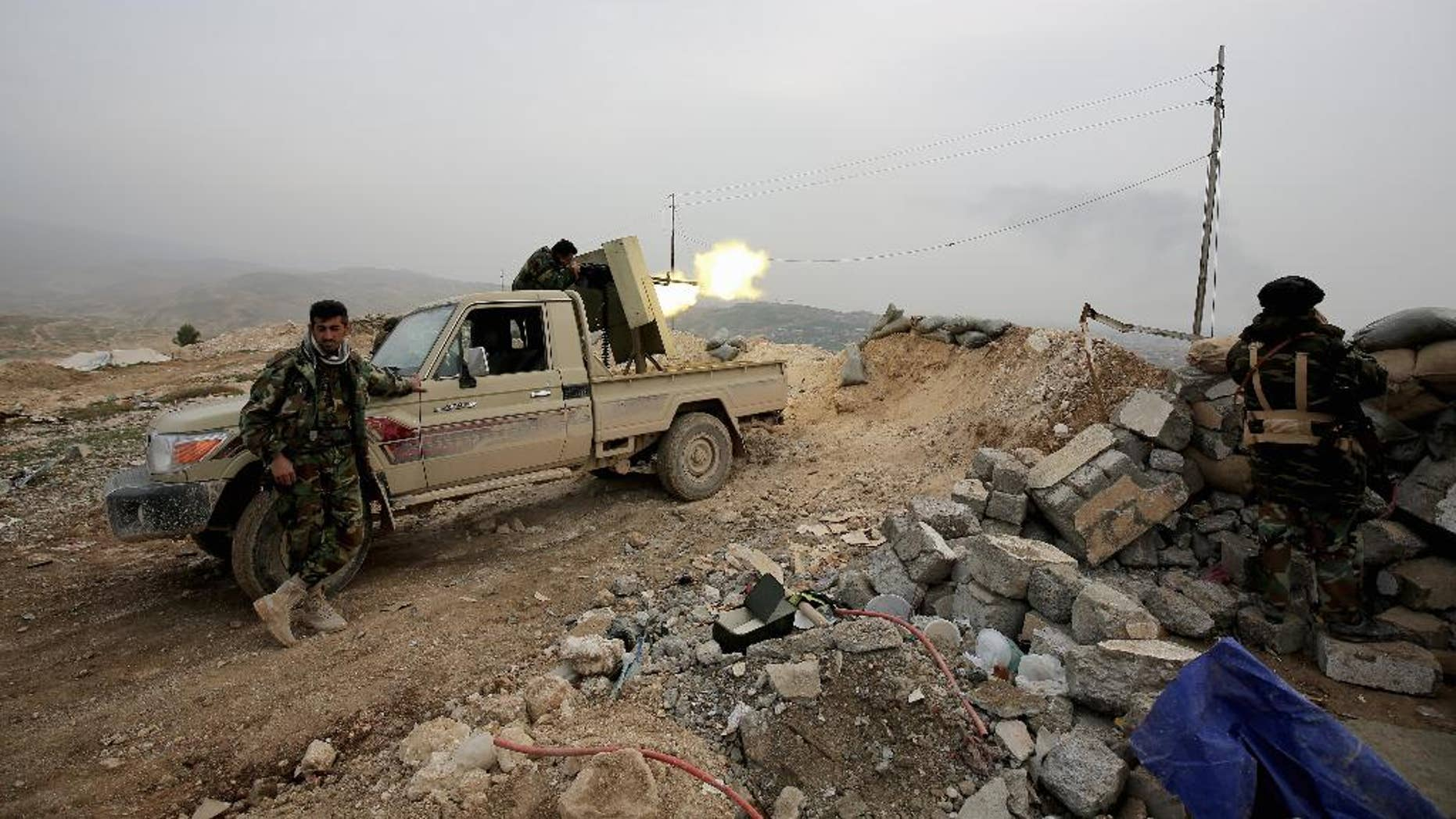Jan. 29, 2015: In this file photo, a Kurdish peshmerga fighter fires a weapon towards positions of the Islamic State group who are 500 meters or half a mile away, overlooking the strategic town of Sinjar, northern Iraq. While Islamic State fighters have been forced to retreat from Kobani, the strategic town on Syria's border with Turkey, they appear far from beaten in northern Iraq.
