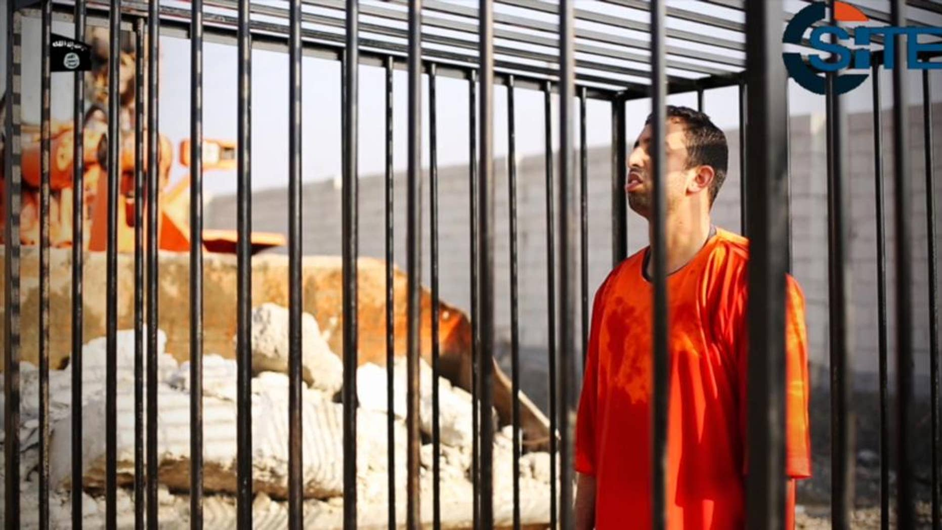 FILE - This still image made from video released by Islamic State group militants and posted on the website of the SITE Intelligence Group in this Tuesday, Feb. 3, 2015 file photo, purportedly shows Jordanian pilot Lt. Muath al-Kaseasbeh standing in a cage just before being burned to death by his captors. The video featured production techniques used in other clips from the militants. But unlike those that showed beheadings in which the hostages or their killer delivered a message before being killed, the pilot video is longer and involves a story-telling narrative and at least four cameras, along with advanced editing techniques. The death of the 26-year-old pilot, who fell into the hands of the militants in December when his Jordanian F-16 crashed near Raqqa, Syria, followed a weeklong drama over a possible prisoner exchange. (AP Photo/SITE Intelligence Group, File)