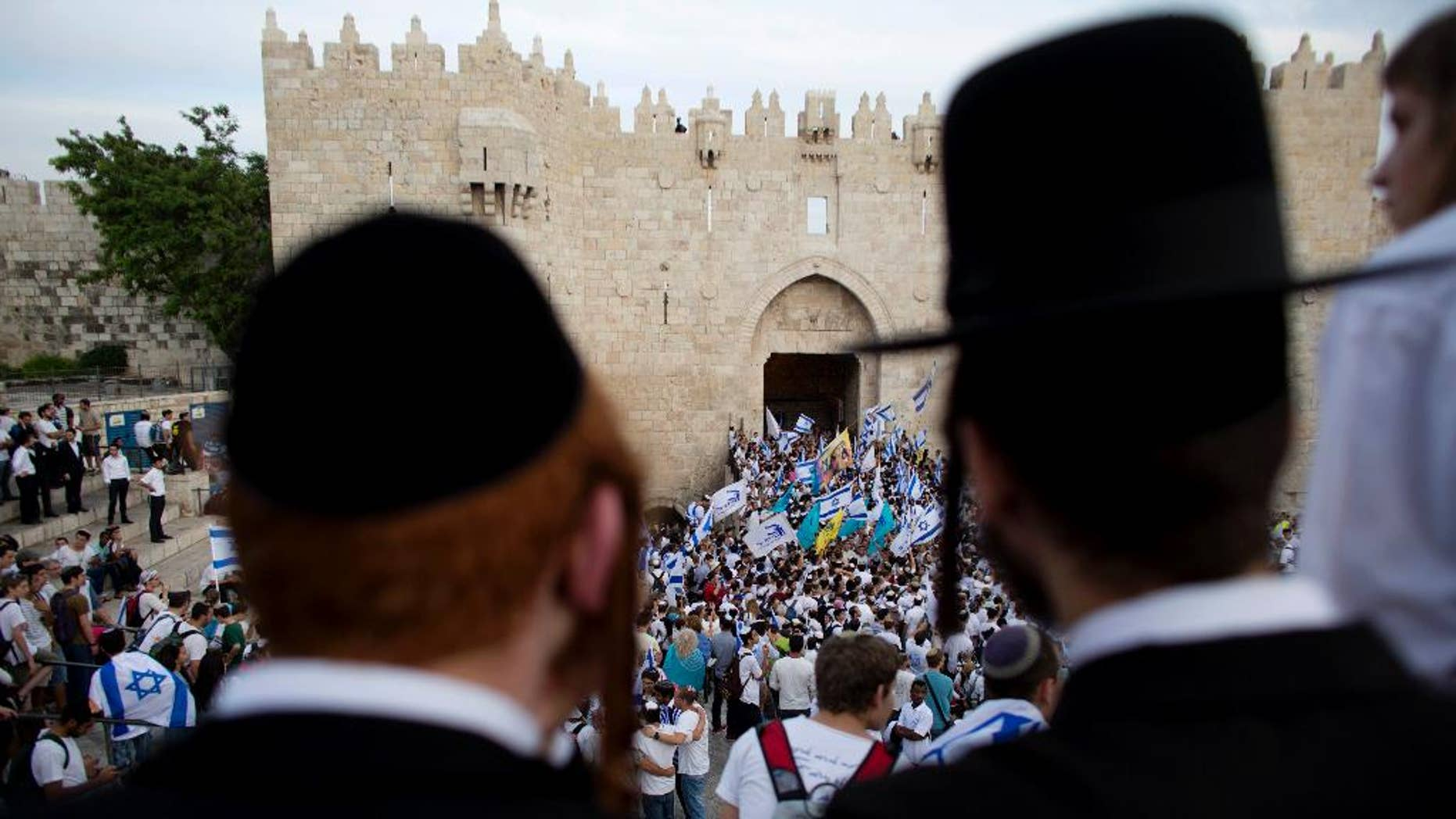 FILE - In this May 28, 2014, file photo, Ultra-Orthodox Jews watch people wave Israeli flags outside the Old City's Damascus Gate during Jerusalem Day celebrations in Jerusalem. A recent demonstration by ultra-Orthodox Jews against a new cinema opening its doors on the Sabbath was meant to be a show of strength in a long-running battle over the role of strict Jewish law in the cultural life of Jerusalem. But in many ways, it was also a sign of desperation after a series of gains by the city's secular community in recent years.  (AP Photo/Dusan Vranic, File)