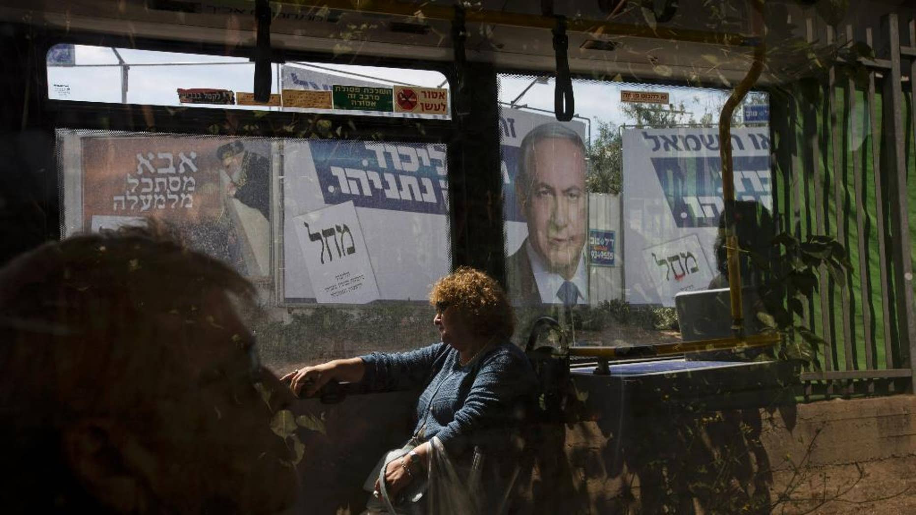 """FILE - In this Monday, March 16, 2015 file photo, passengers sit in a bus driving past a billboard with the photo of Israeli Prime Minister Benjamin Netanyahu, right, and late rabbi Ovadia Yosef, a long time spiritual leader of the Shas party, a day ahead of legislative elections, in Bnei Brak near Tel Aviv, Israel. The displeasure felt in some quarters over  Netanyahu's win last week has placed front and center the world community's unwritten obligation to accept the results of a truly democratic vote. It is a basic tenet of the modern world order which has survived the occasional awkward result _ as well as recent decades' emergence of some less-than-pristine democracies around the globe.  The Hebrew sign at left reads, """" Father is looking from above.'' At right Hebrew reads, """"Likud, Netanyahu."""" (AP Photo/Ariel Schalit, File)"""