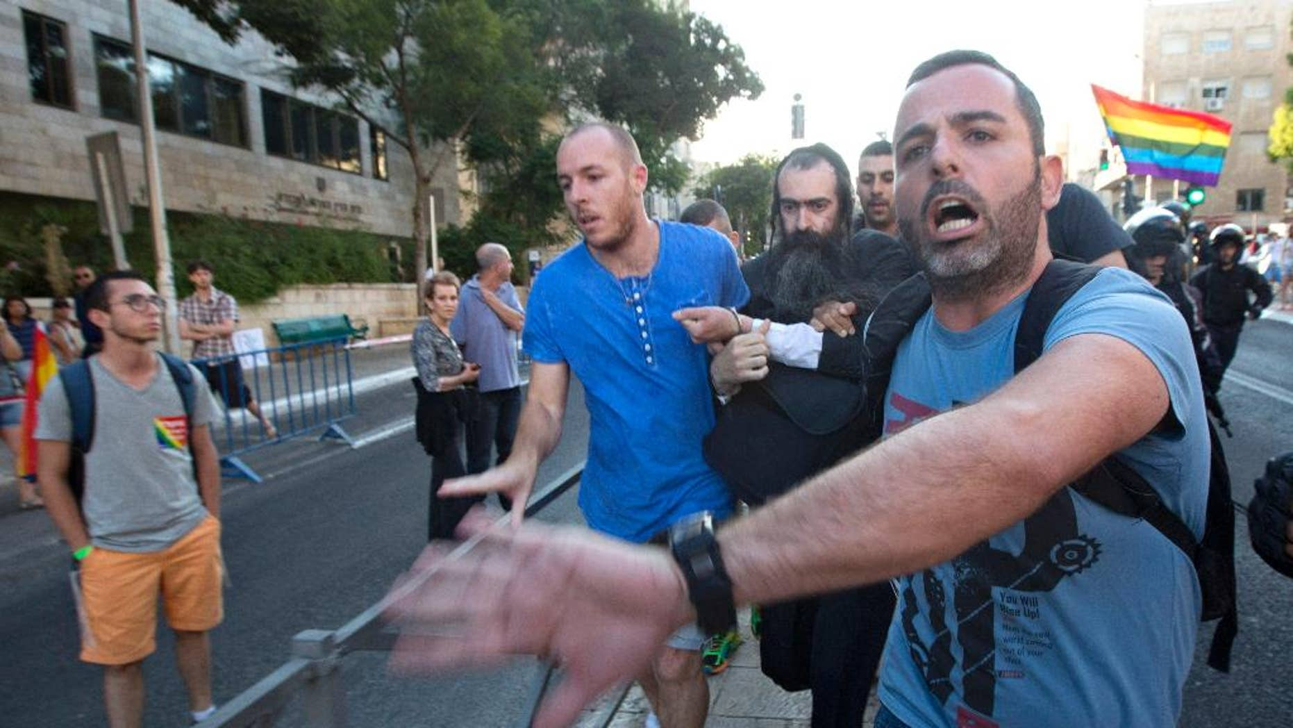 FILE - In this July 30, 2015 file photo, plainclothes Israeli police detain Yishai Schlissel, an ultra-Orthodox Jew, after he attacked people with a knife during a Gay Pride parade, in central Jerusalem. One of them, 16-year-old Shira Banki, later died of her wounds. Jerusalem's District Court indicted Schlissel for Banki's murder on Monday, Aug. 24, 2015, along with multiple attempted murder charges for those he wounded. Schlissel, who had been freed from prison weeks earlier after serving a sentence for stabbing several people at the city's pride parade in 2005. (AP Photo/Sebastian Scheiner, File)